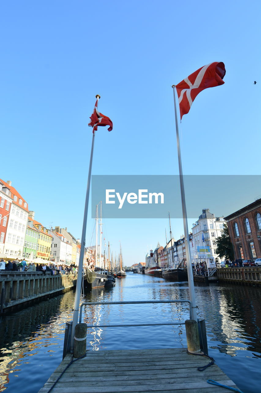 Low angle view of danish flag by canal against clear sky