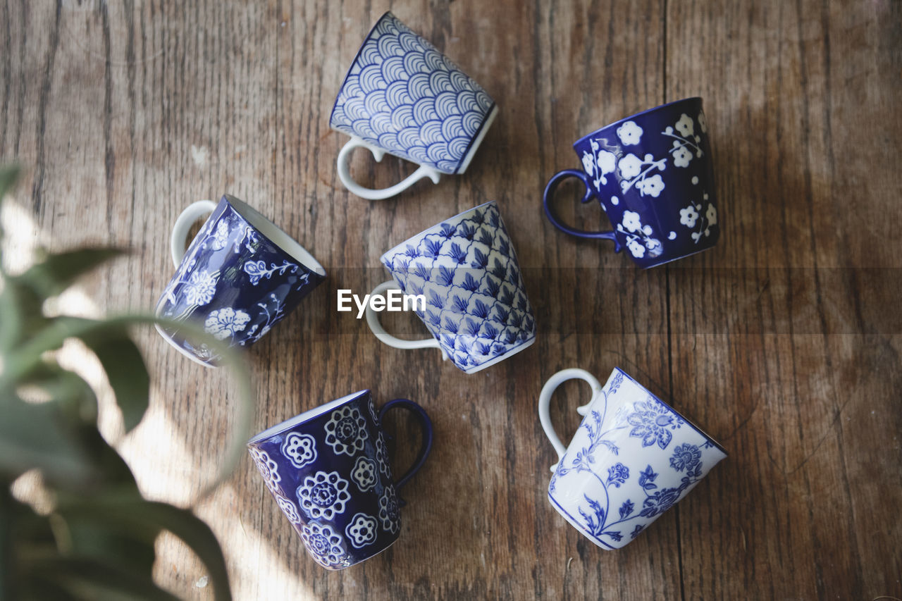 High Angle View Of Blue Cups On Wooden Table