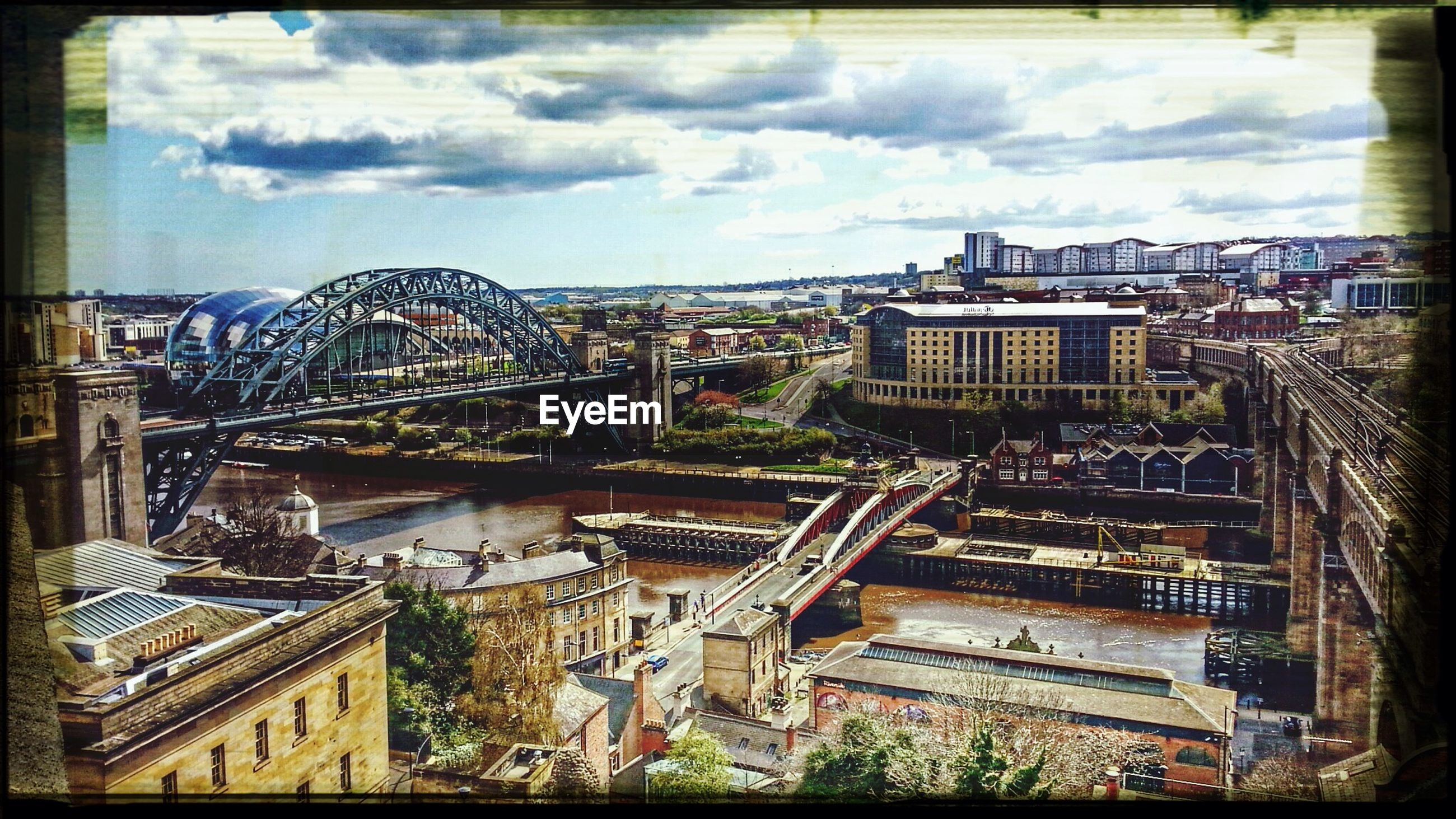 transfer print, architecture, auto post production filter, built structure, building exterior, sky, cloud - sky, city, cloudy, day, outdoors, cloud, panoramic, no people, metal, tower, travel destinations, building, low angle view, construction site
