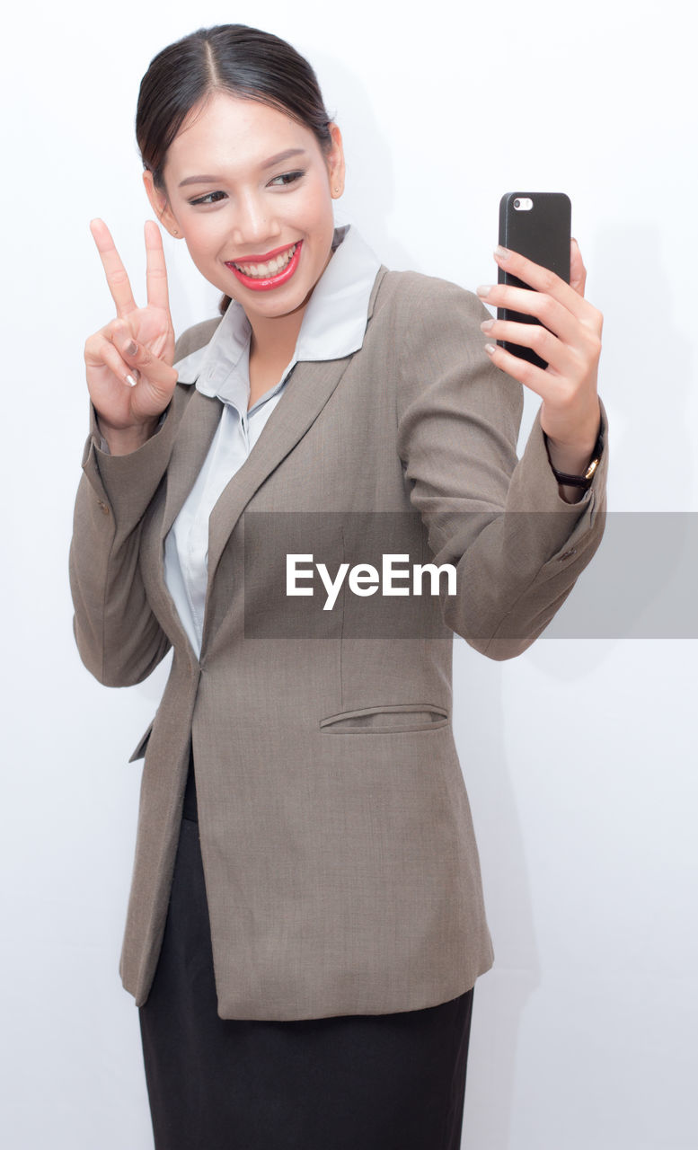 Businesswoman using mobile phone while standing against white background