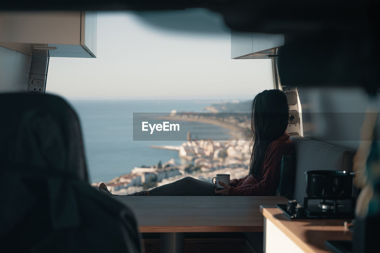 Rear view of woman sitting at table in bus by sea against sky