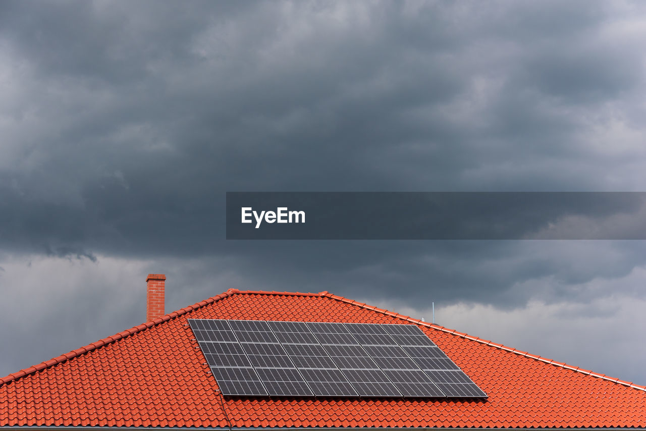 Red tile roof with photovoltaic panels during stormy weather, solar pv installation dark blue clouds
