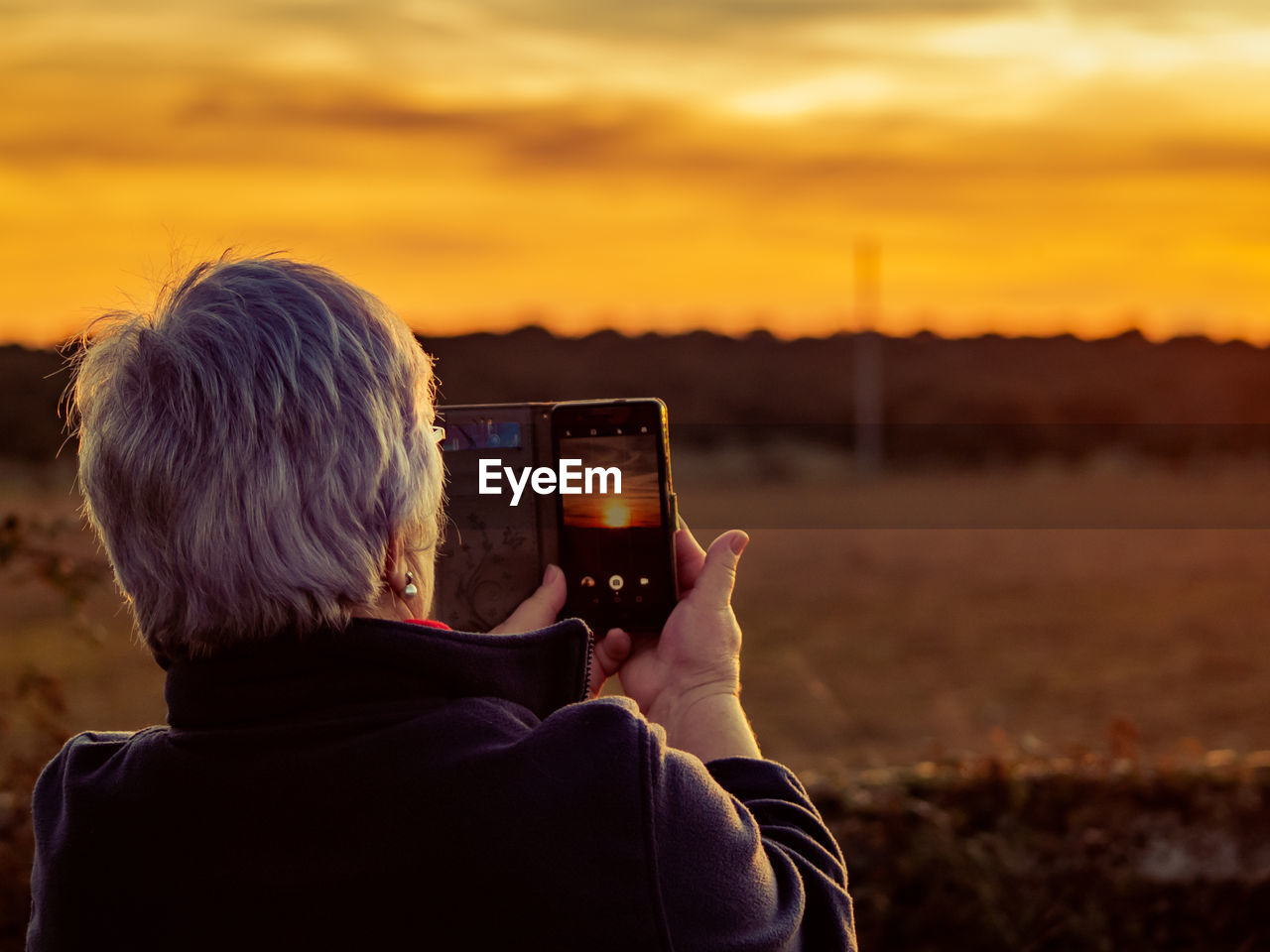 Rear view of woman photographing with mobile phone against orange sky