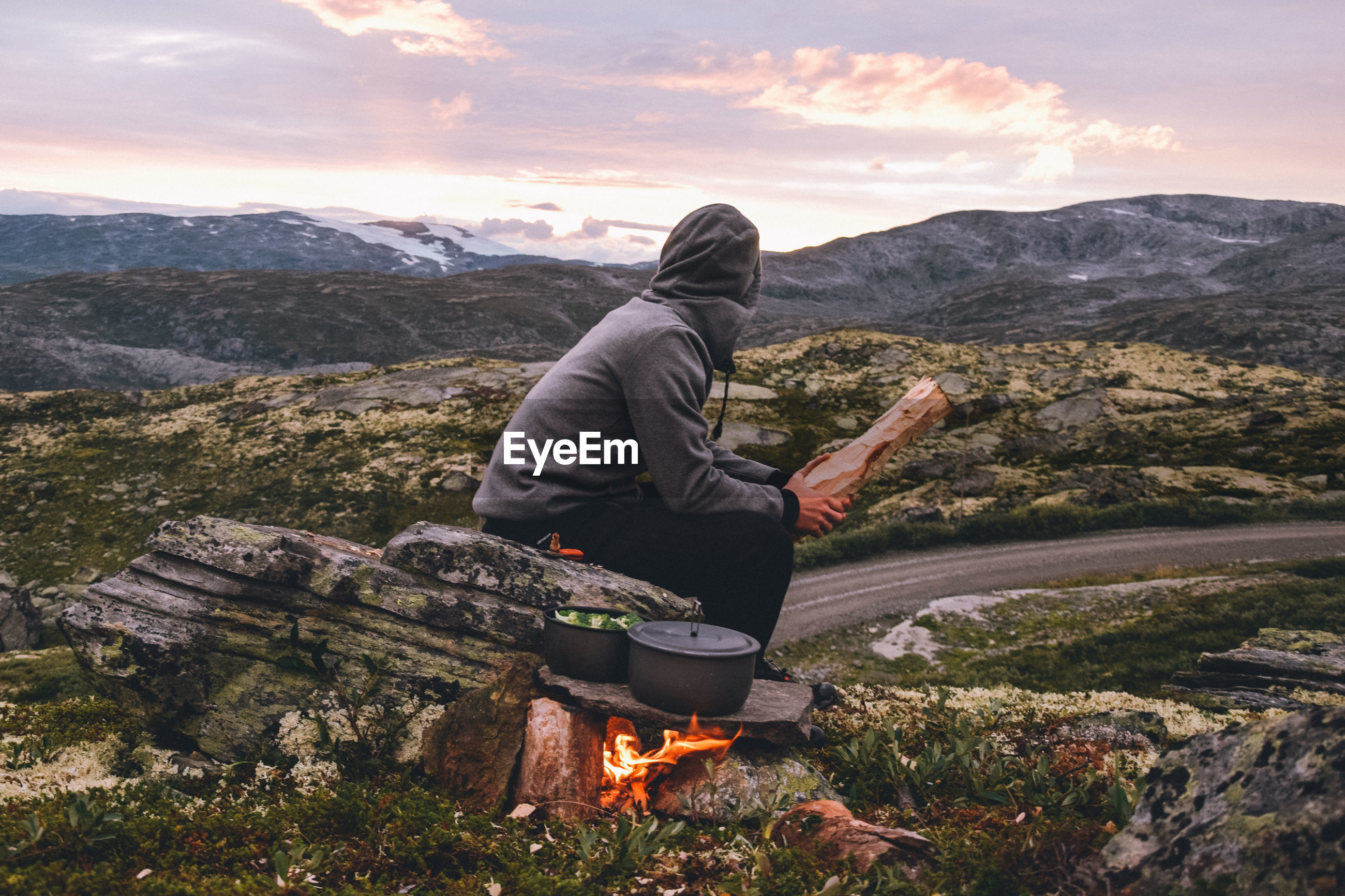 Full length of man sitting by fire against mountains and sky