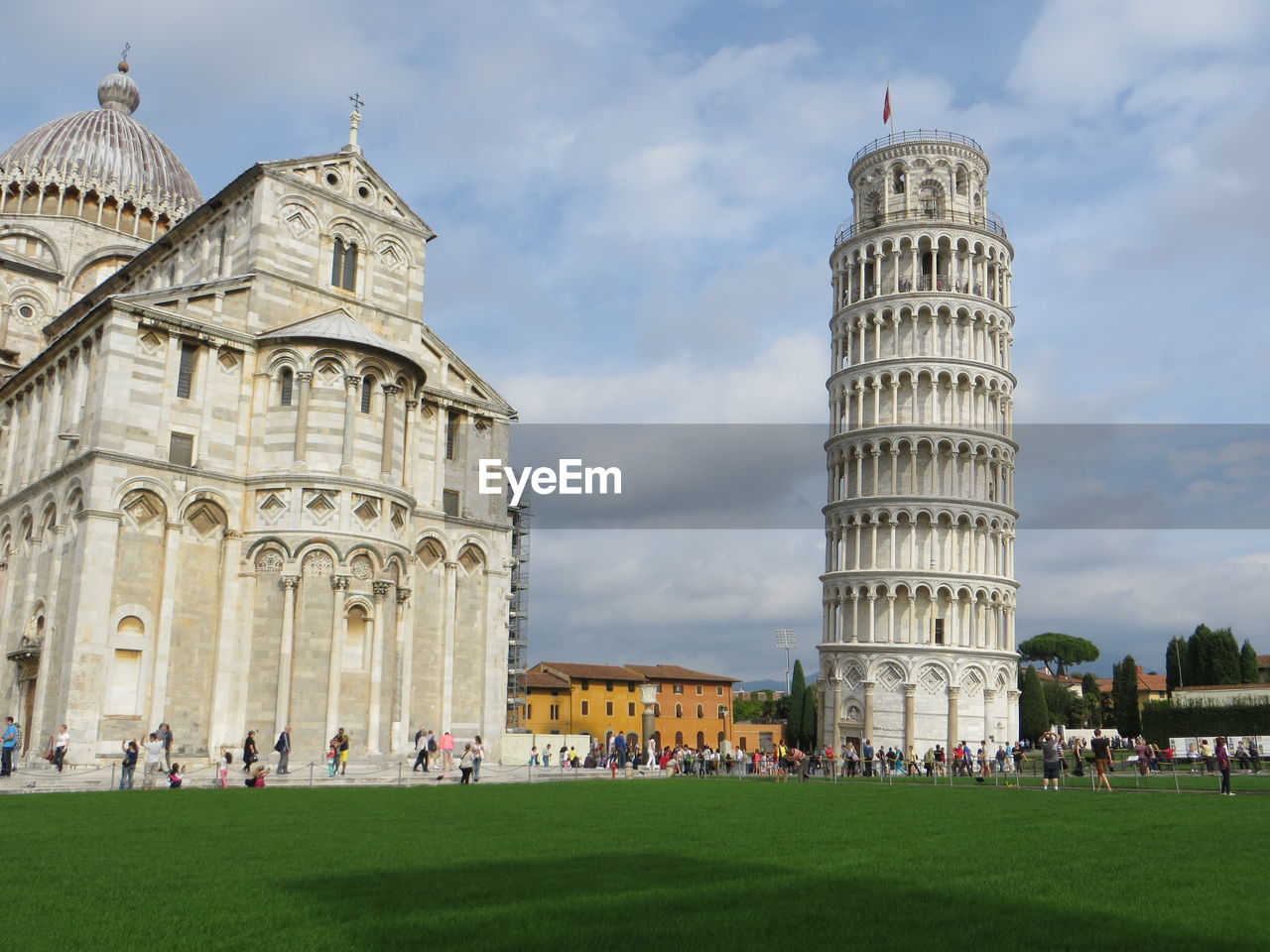 Leaning tower of pisa and cathedral against cloudy sky at piazza dei miracoli