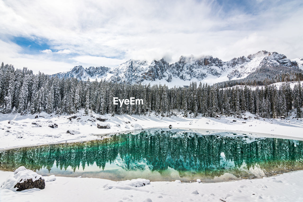 winter, cold temperature, snow, beauty in nature, scenics - nature, tranquil scene, sky, tranquility, mountain, cloud - sky, nature, environment, tree, non-urban scene, frozen, no people, water, white color, plant, snowcapped mountain, pine tree, powder snow