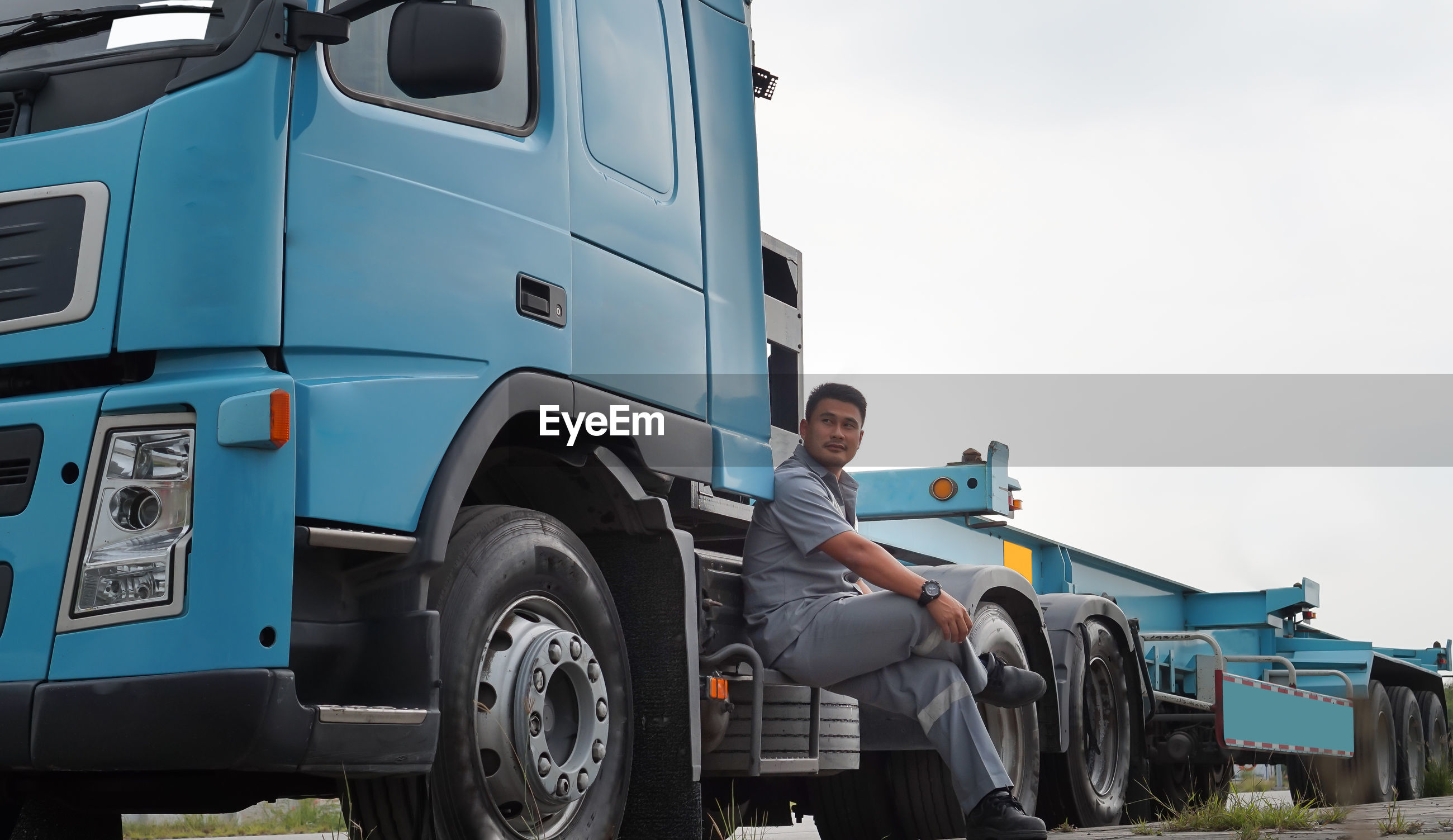 Side view of man looking away while sitting on truck against clear sky