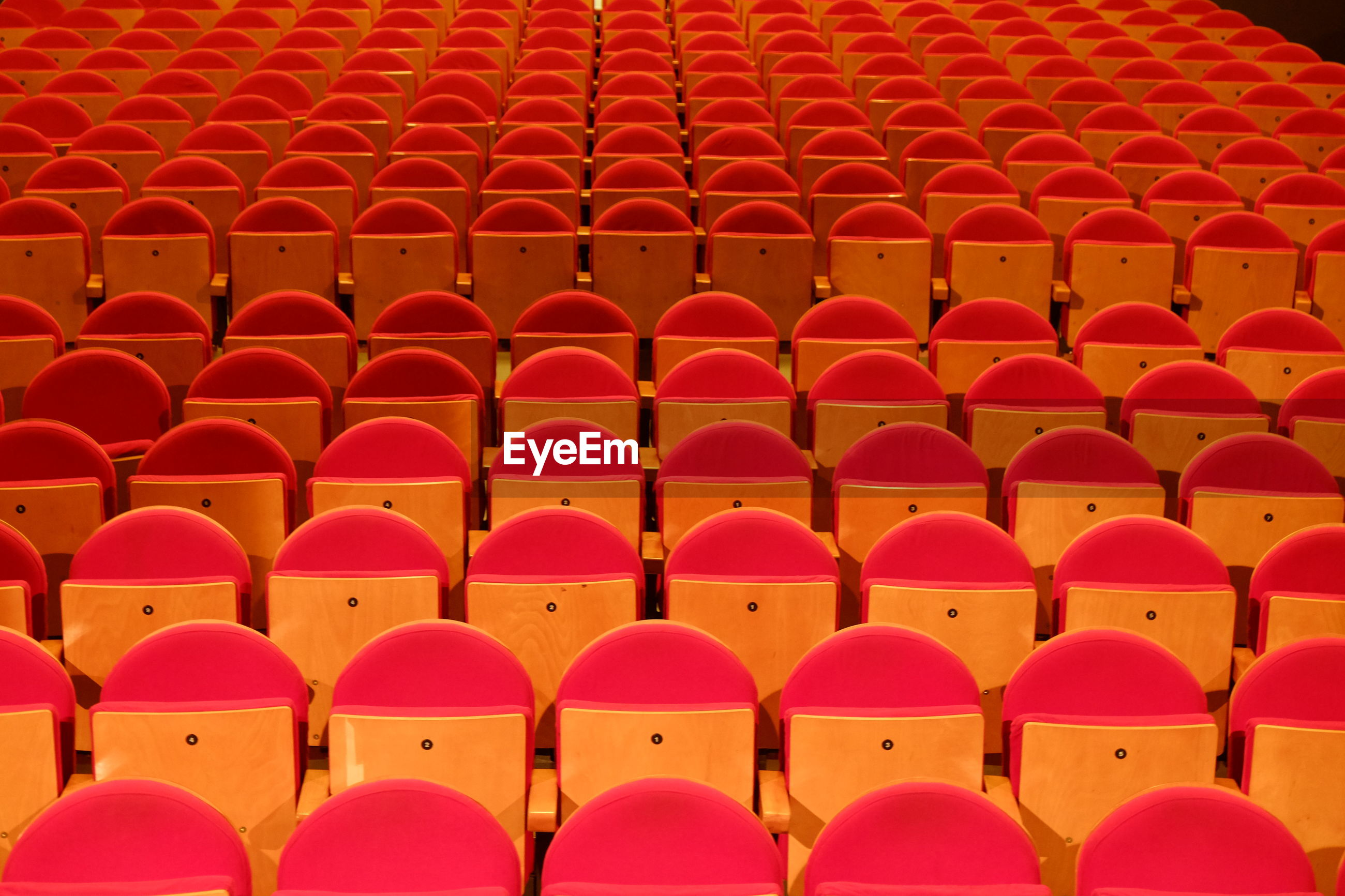 Close-up of red seats in a theatre.