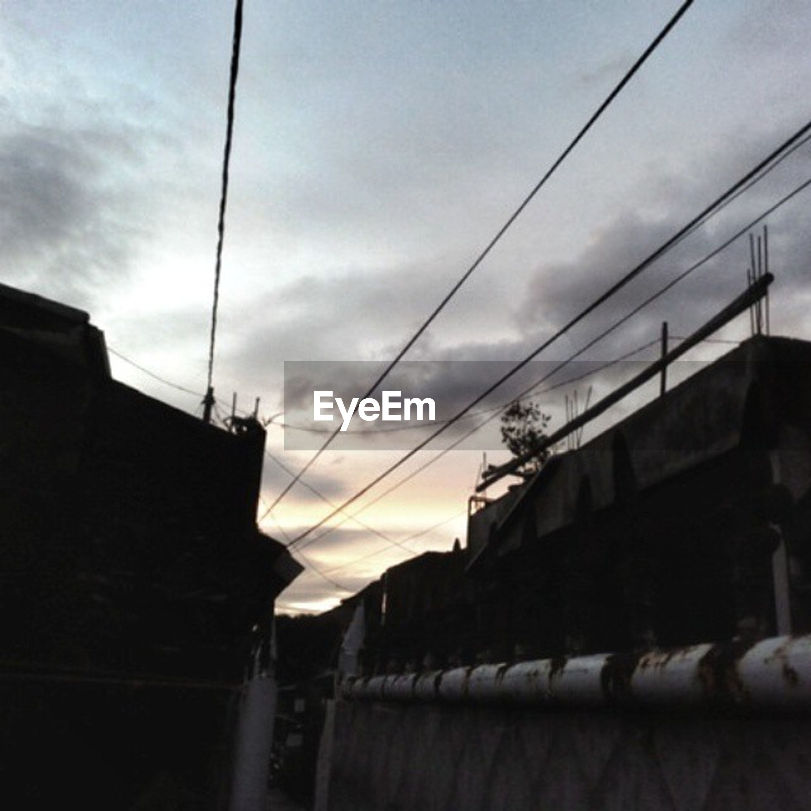 sky, power line, built structure, architecture, building exterior, cable, cloud - sky, low angle view, electricity pylon, cloud, house, power supply, electricity, connection, residential structure, cloudy, transportation, power cable, no people, silhouette