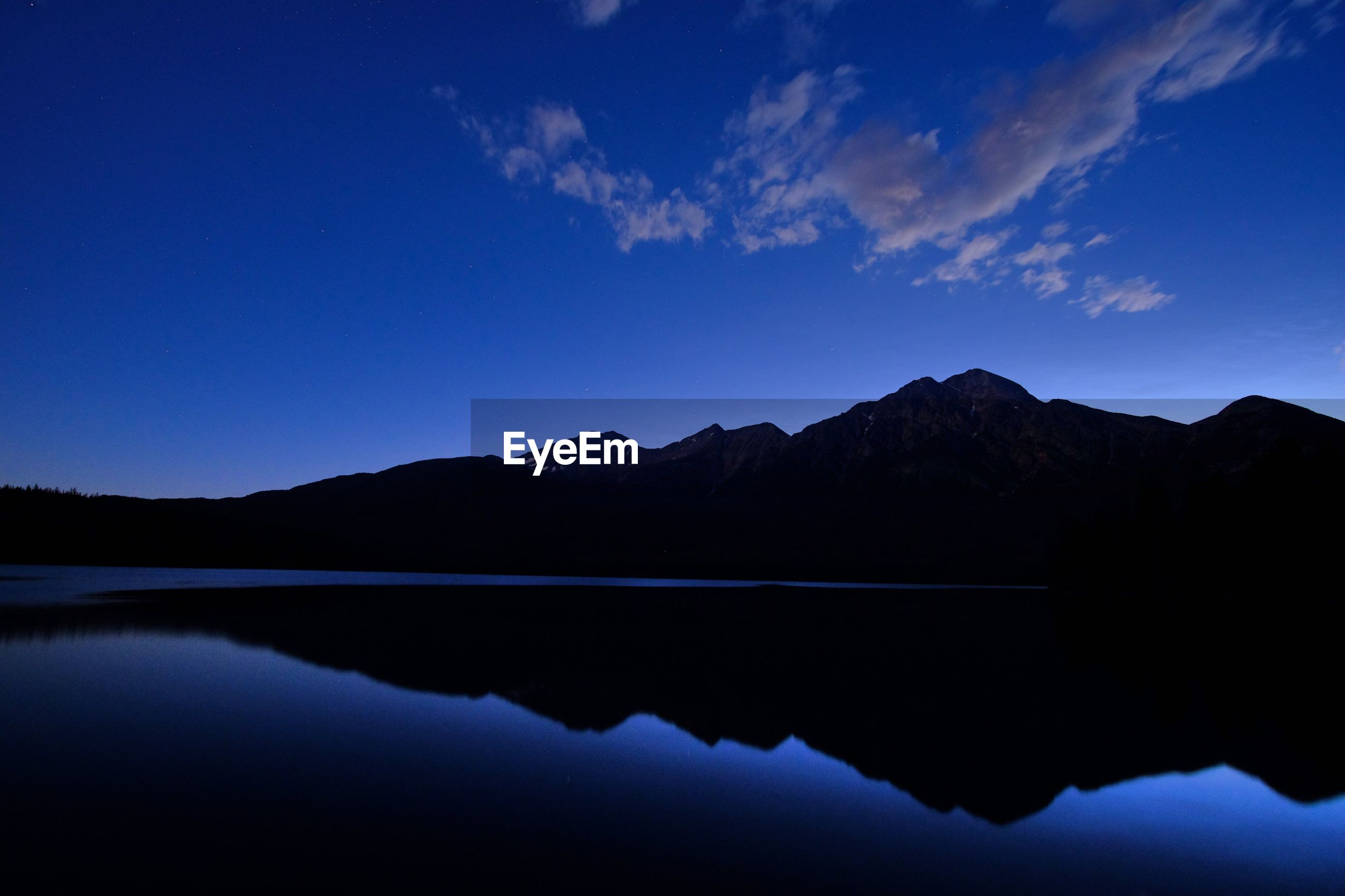 SCENIC VIEW OF LAKE BY SILHOUETTE MOUNTAINS AGAINST BLUE SKY