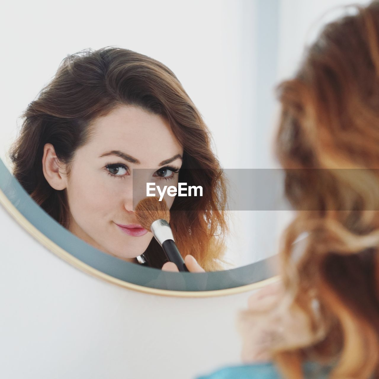 Close-Up Of Young Woman With Make-Up Brush In Front Of Mirror