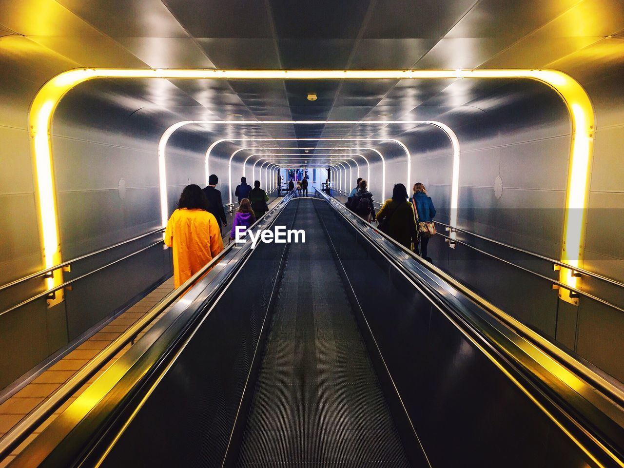 Rear View Of People Standing On Escalator