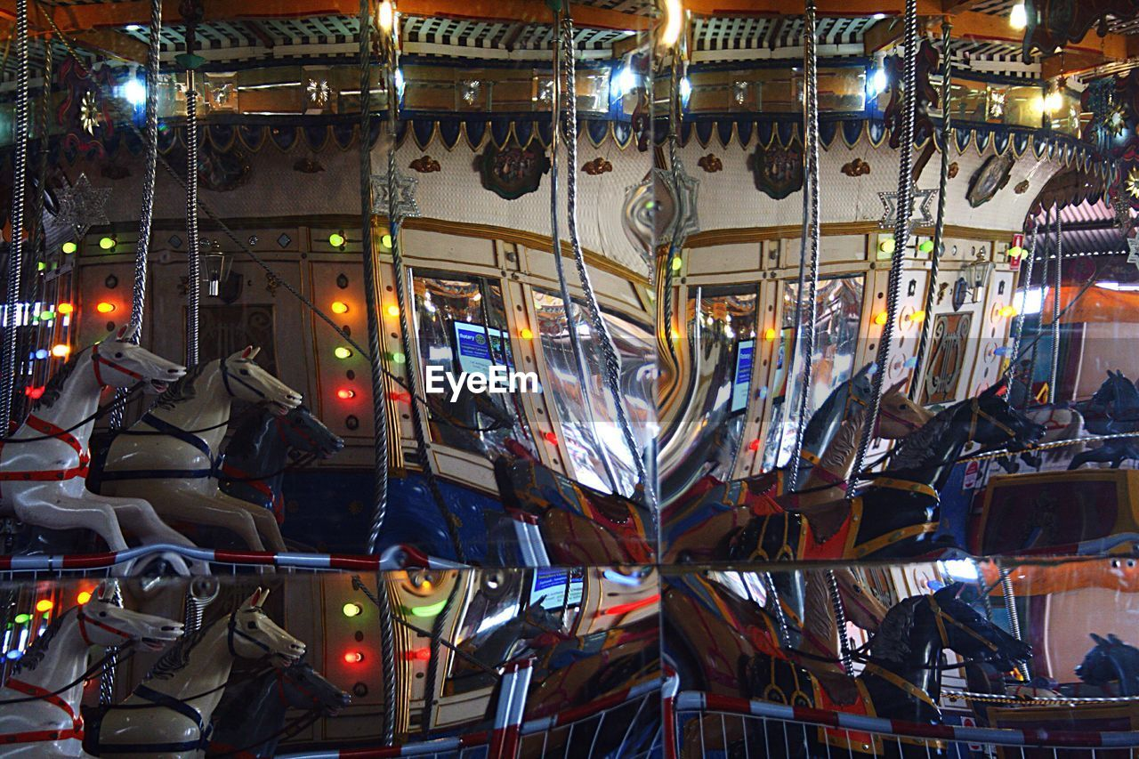 Reflection Of Carousel On Mirror At Amusement Park