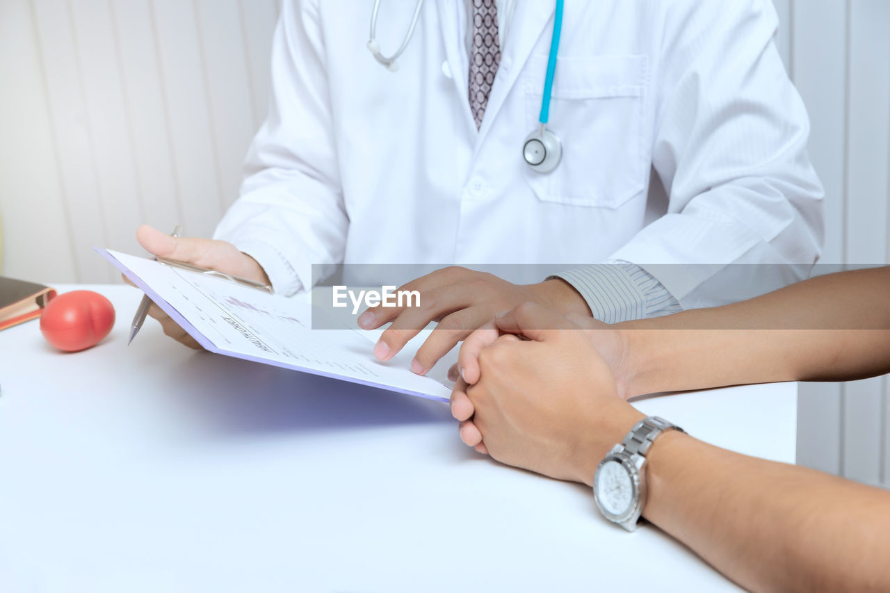 Midsection of doctor explaining medical records to patient