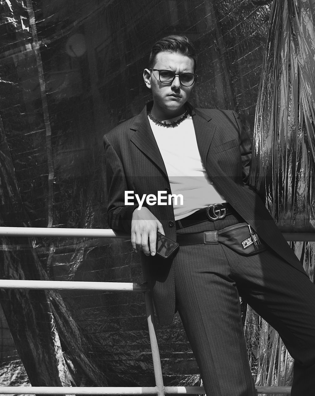 young adult, young men, one person, glasses, front view, lifestyles, real people, three quarter length, fashion, looking at camera, leisure activity, sunglasses, standing, men, portrait, clothing, railing, casual clothing, outdoors, hairstyle, contemplation