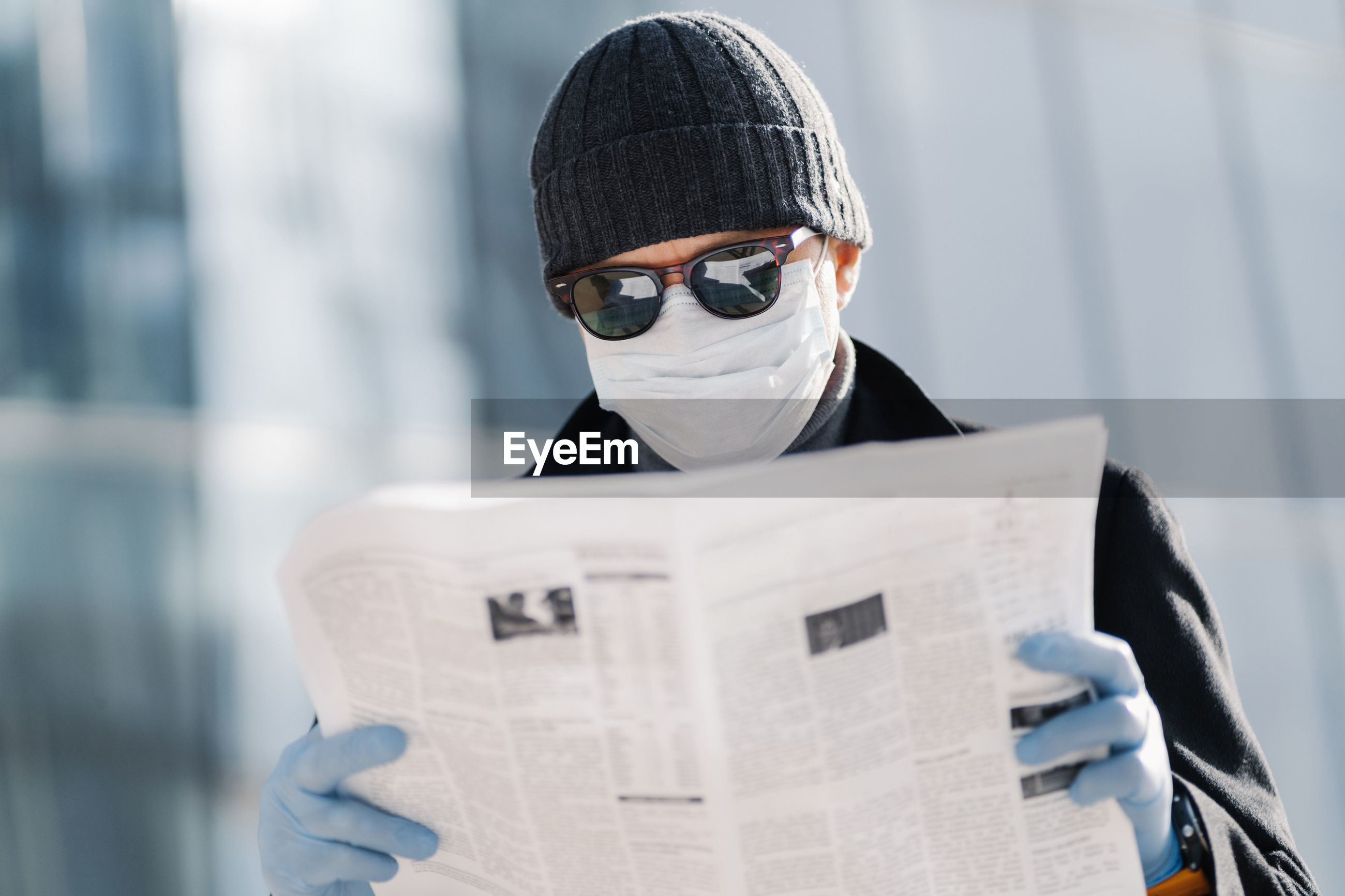 Man wearing mask reading newspaper in city