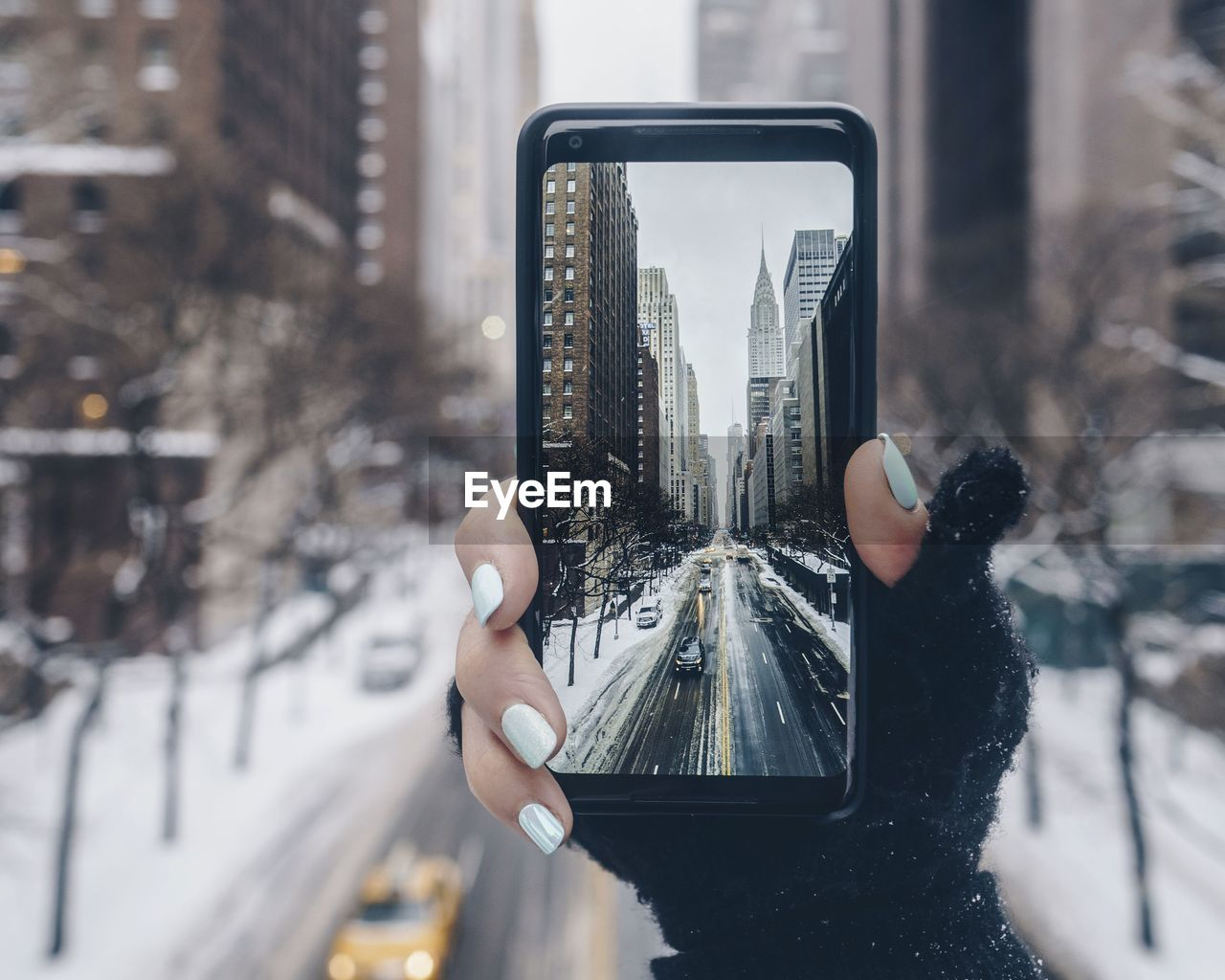 Close-Up Of Woman Photographing Through Smart Phone In Winter