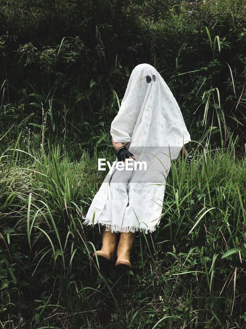 Person disguised as ghost for halloween in green grass field