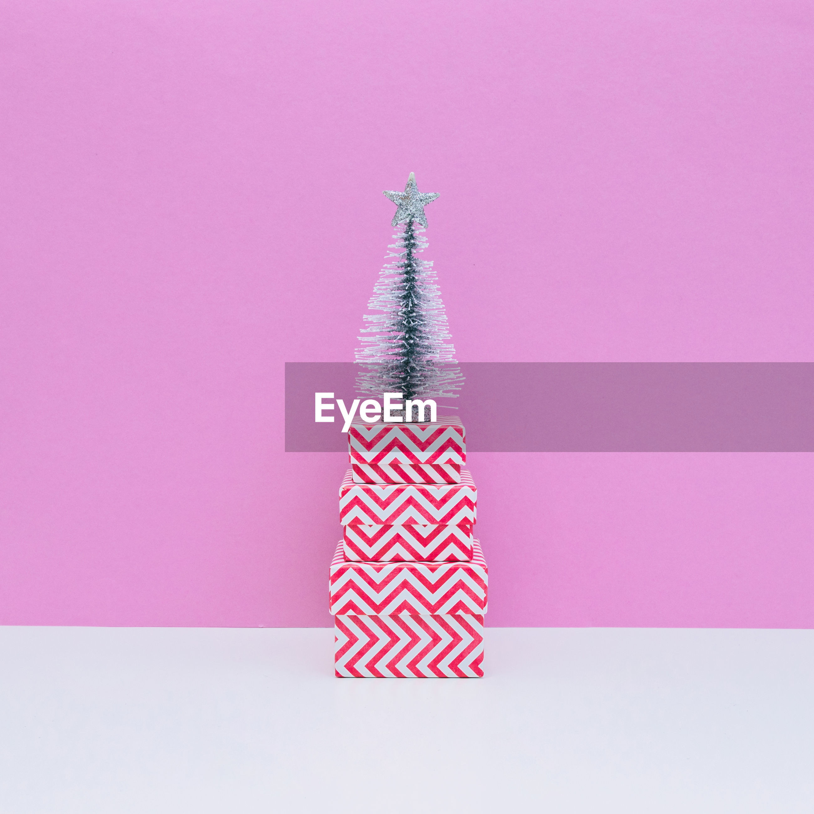 Christmas tree on stacked gifts against pink background