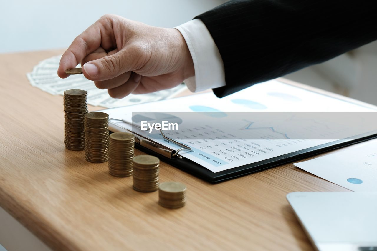human hand, hand, table, one person, human body part, business, men, real people, finance, indoors, holding, wood - material, coin, human finger, business finance and industry, publication, finger, body part, adult