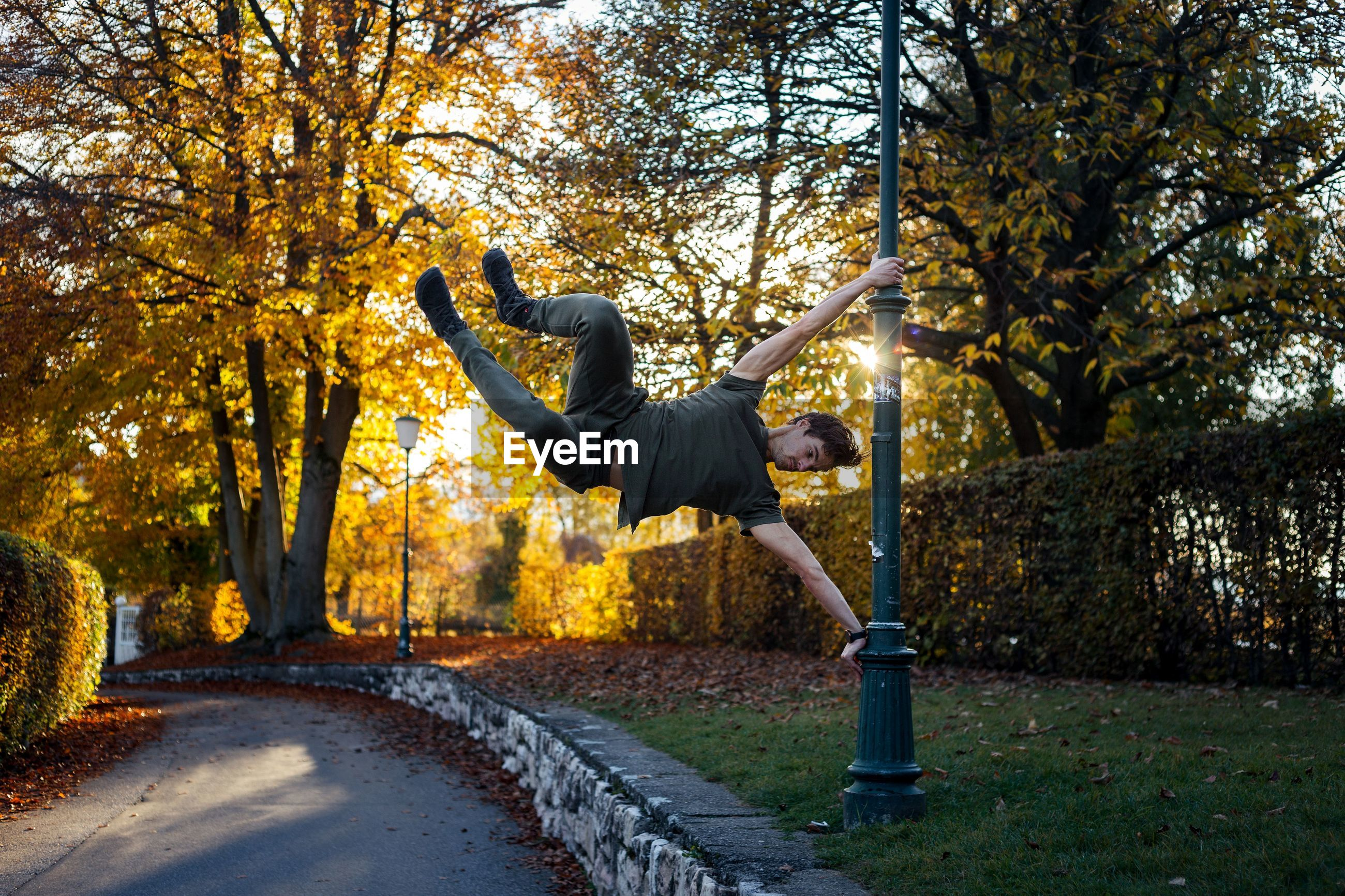Man hanging on pole in park during autumn