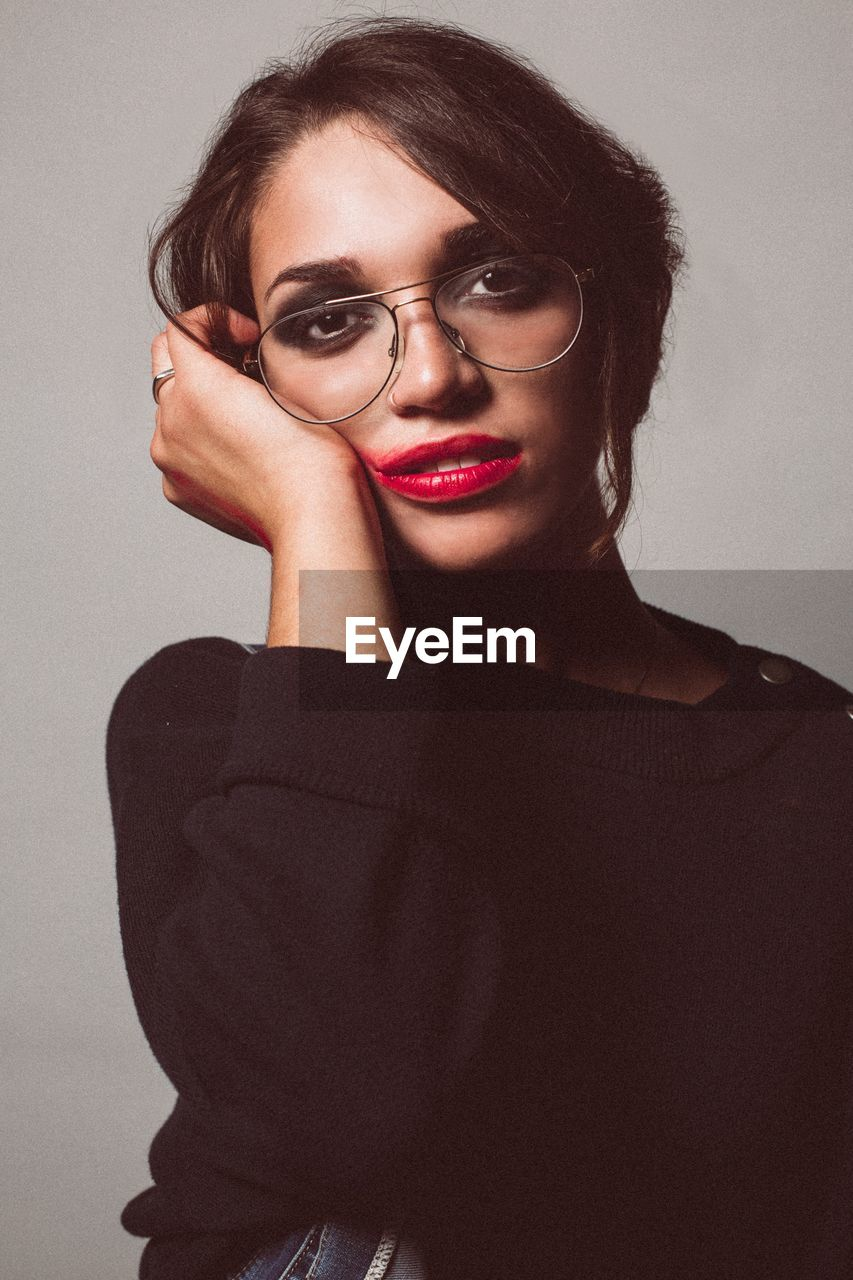one person, portrait, glasses, front view, young women, looking at camera, indoors, young adult, lifestyles, women, adult, leisure activity, make-up, smiling, beautiful woman, standing, casual clothing, eyeglasses, lipstick, fashion, hairstyle