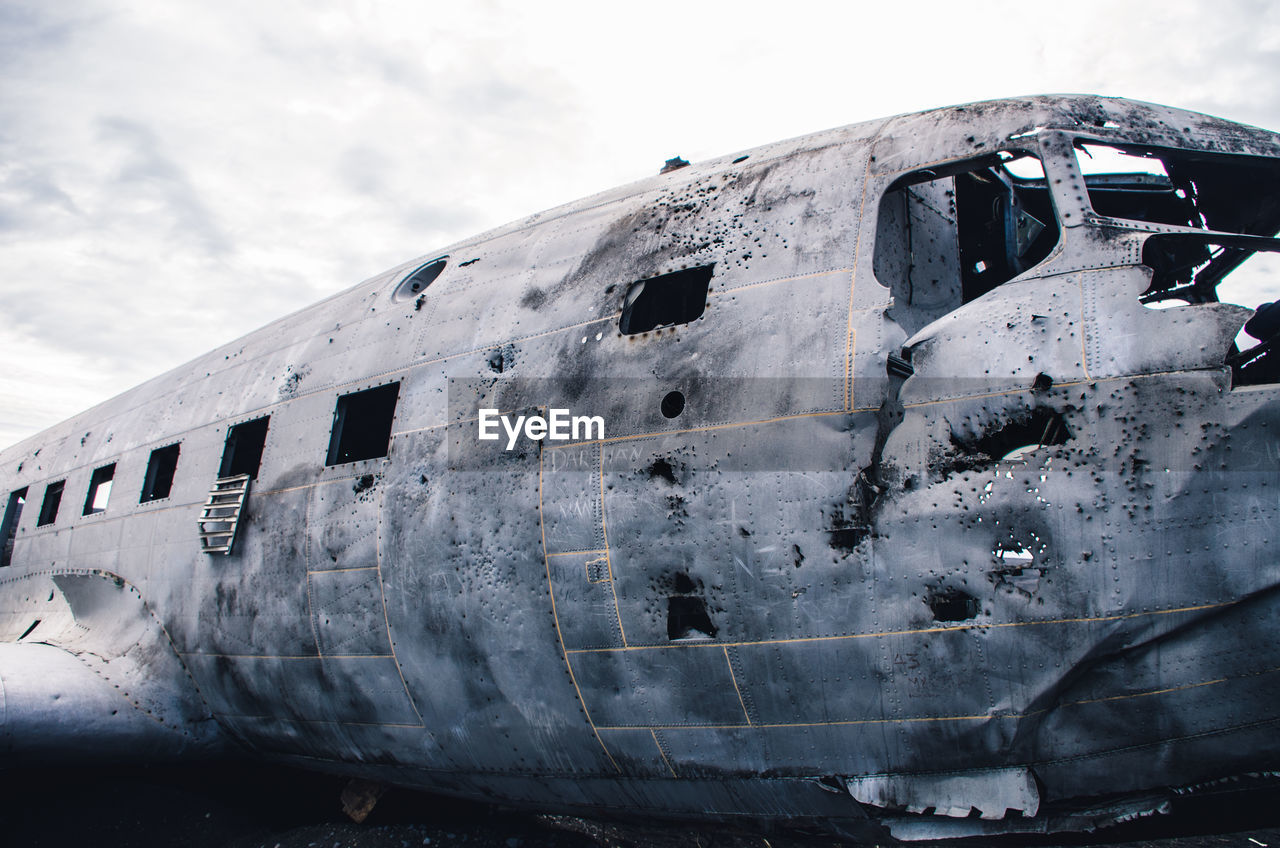 Abandoned Airplane Against Cloudy Sky