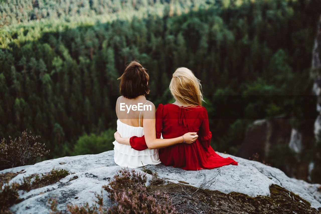 Rear View Of Women Sitting On Rock At Mountain