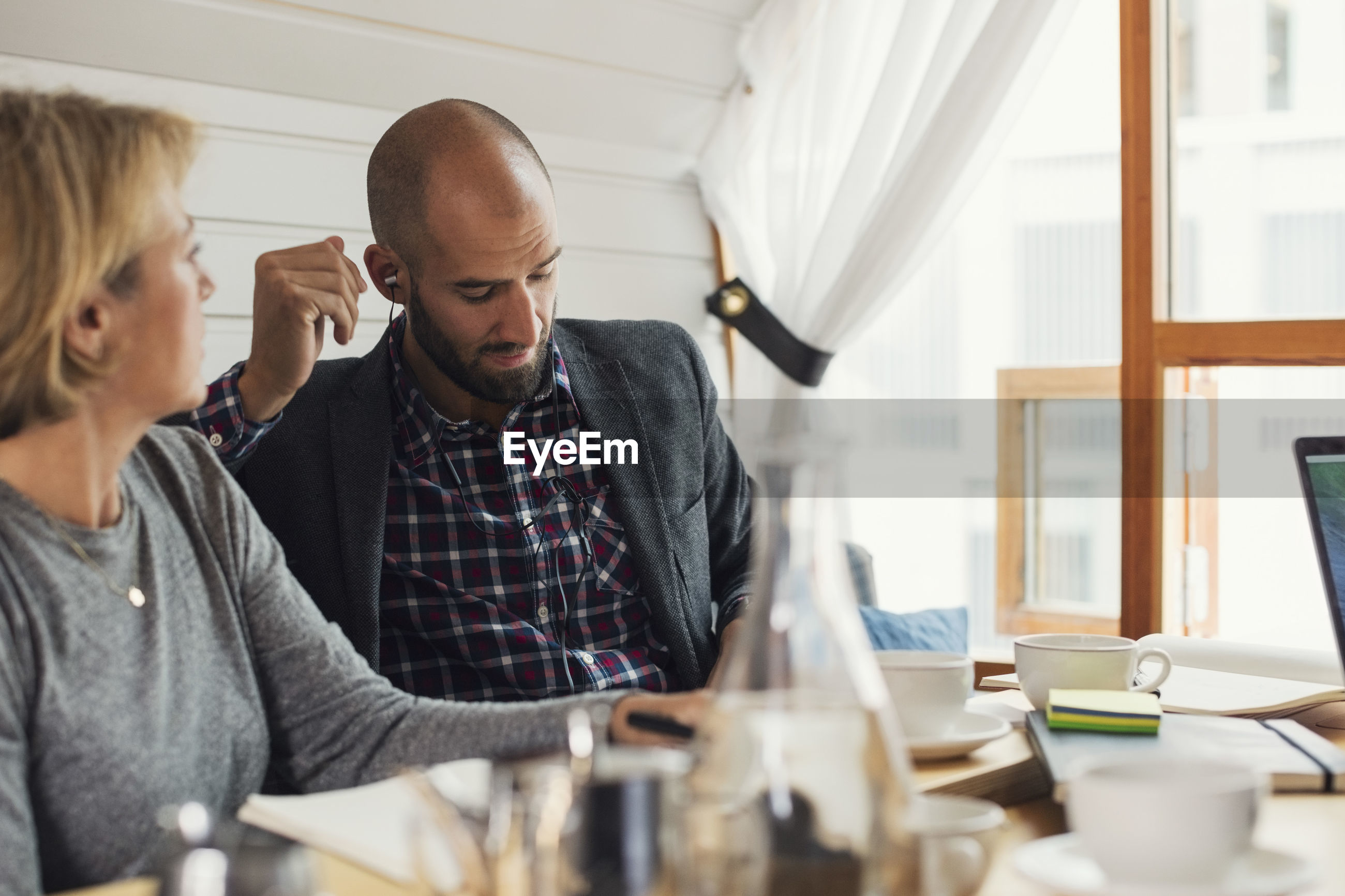 Mid adult businessman wearing in-ear headphones while sitting by female colleague in office