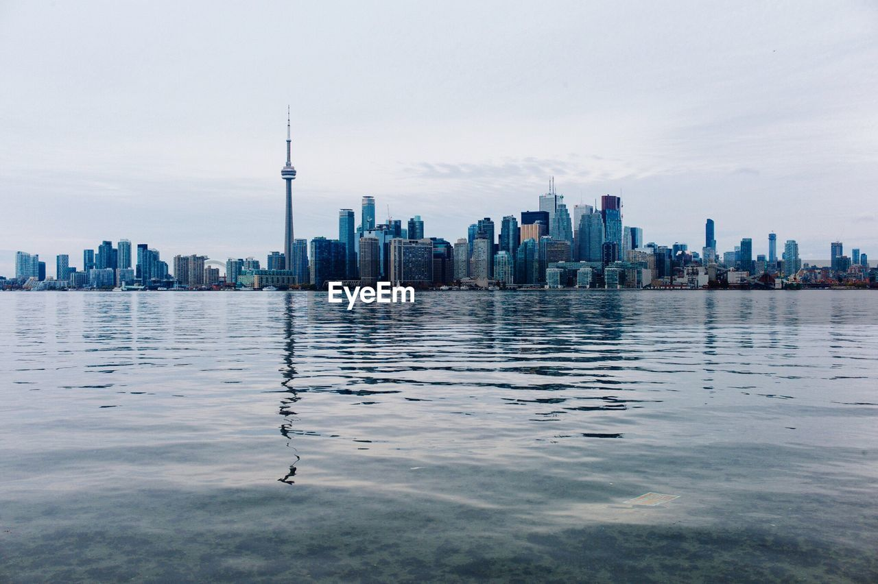 Cn Tower With Cityscape By River Against Sky