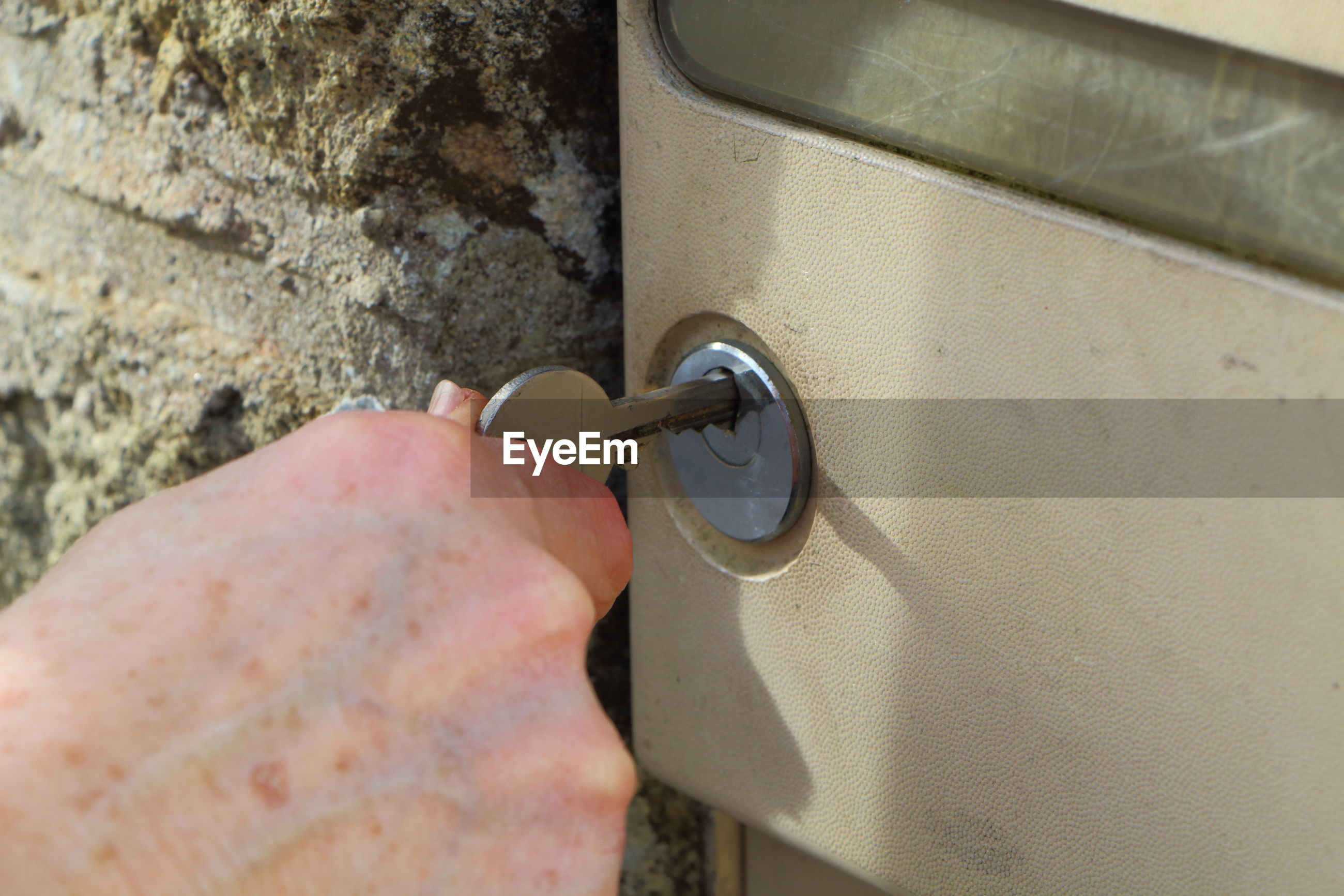 Cropped hand of person inserting key in hole on door
