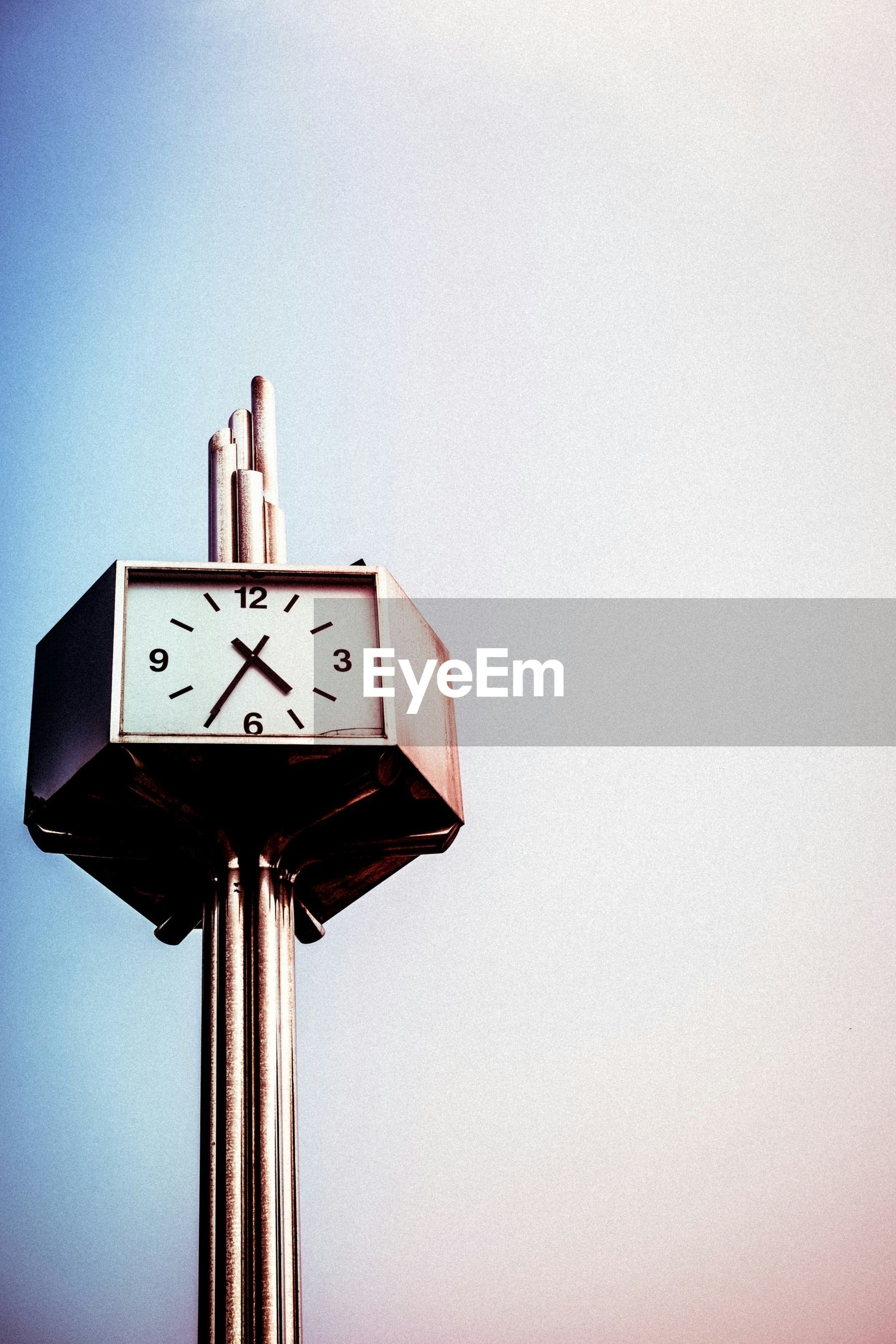Low angle view of clock on pole against clear sky