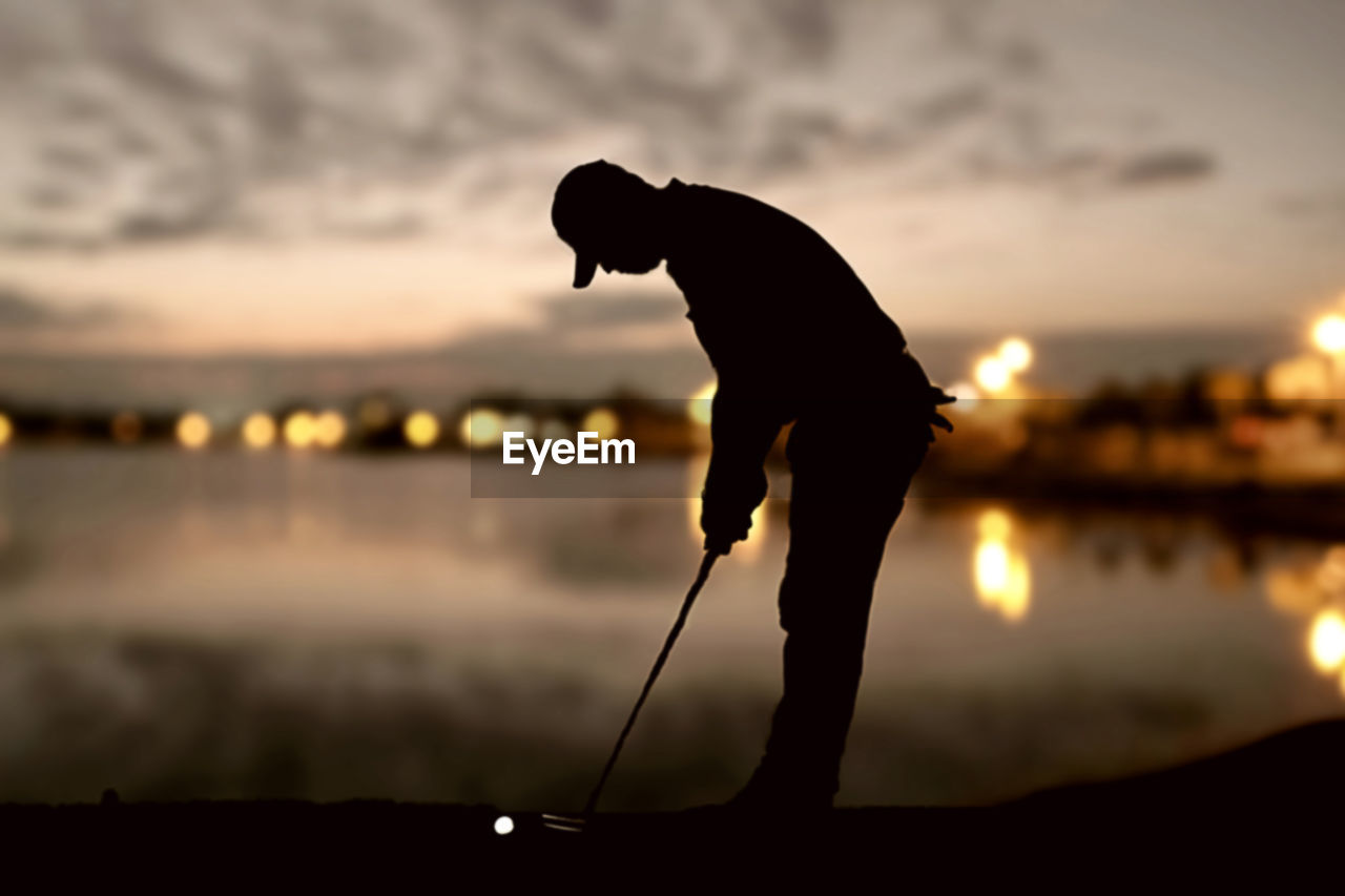 Silhouette Man Playing Golf At Sunset