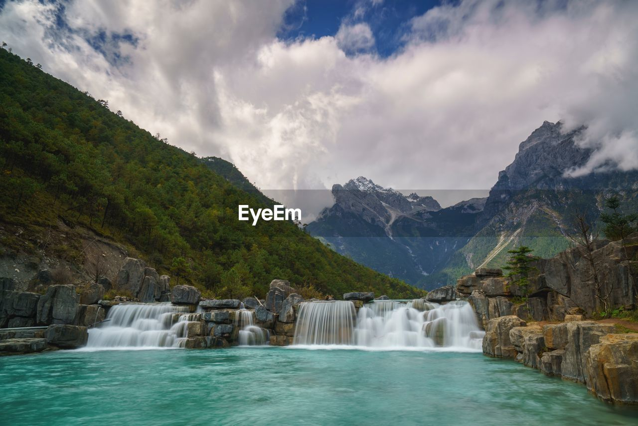 water, mountain, beauty in nature, cloud - sky, scenics - nature, sky, nature, motion, waterfall, long exposure, tranquil scene, no people, mountain range, day, waterfront, tranquility, non-urban scene, flowing water, idyllic, outdoors, flowing, turquoise colored, power in nature