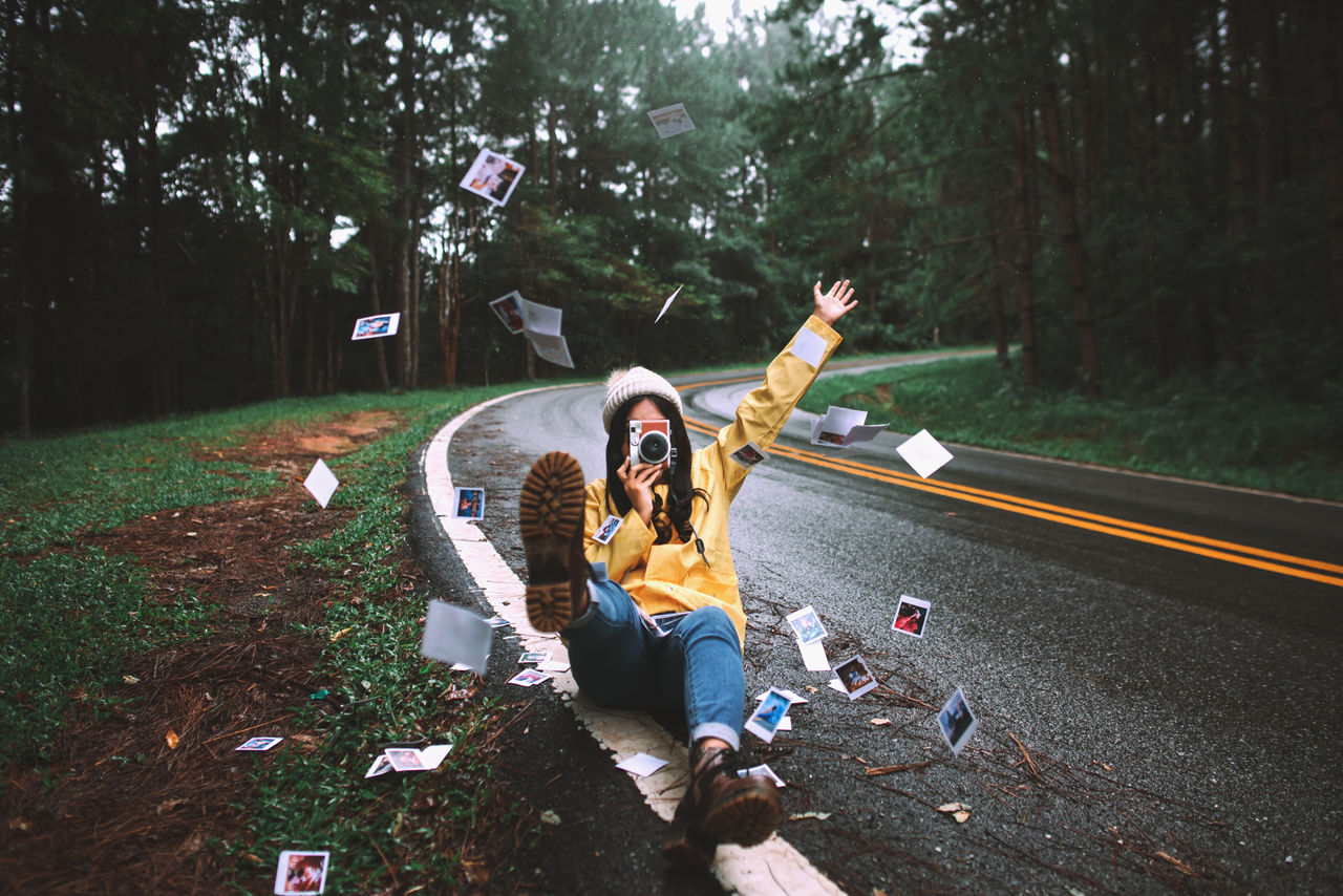 Full length of young woman photographing from camera while sitting amidst instant print transfers on road at forest