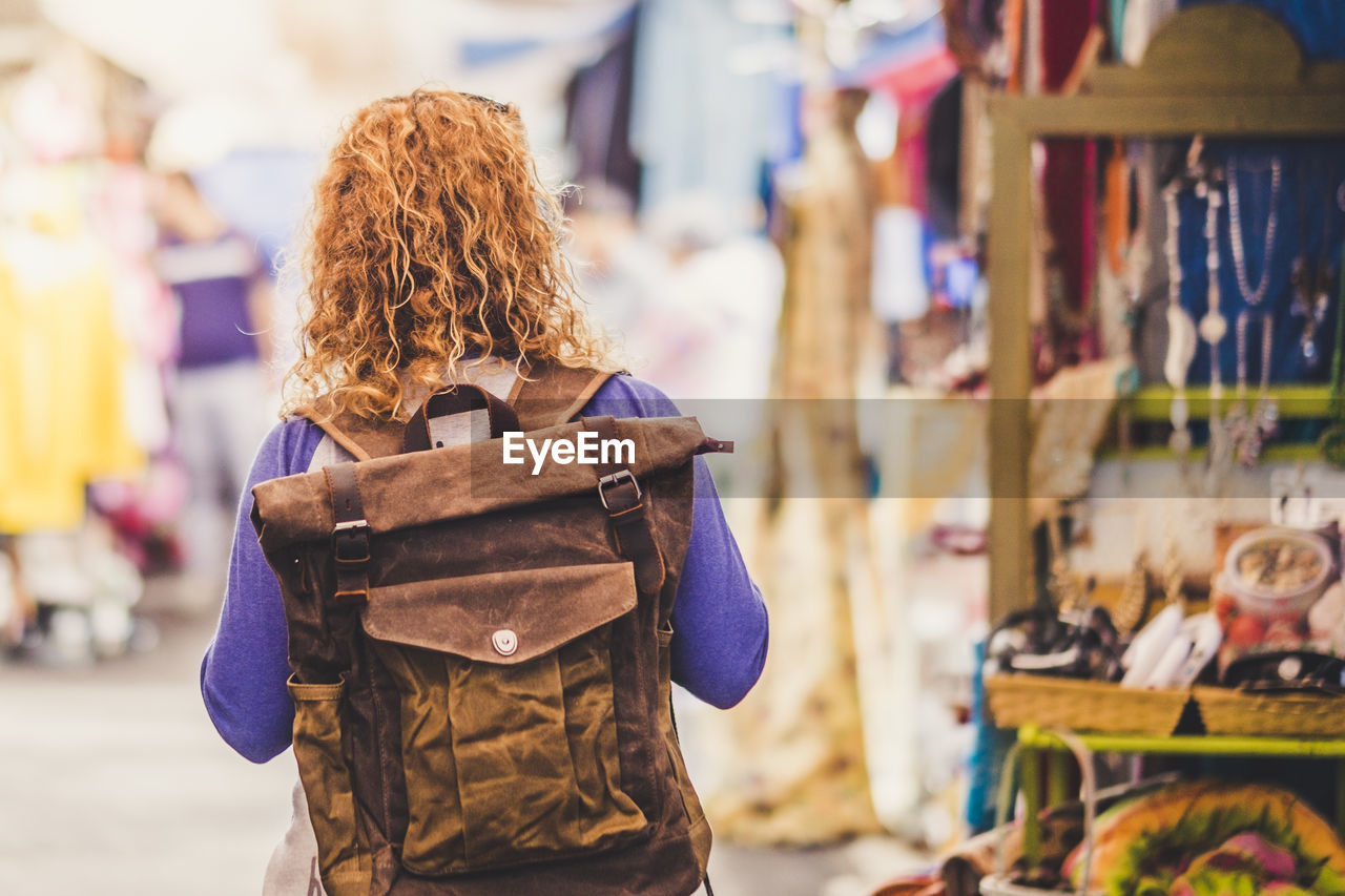 one person, focus on foreground, real people, hairstyle, leisure activity, hair, market, lifestyles, women, retail, adult, curly hair, day, rear view, waist up, incidental people, standing, bag, brown hair, outdoors, warm clothing