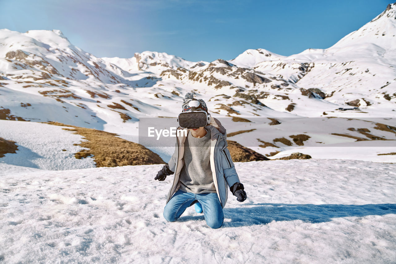 REAR VIEW OF MAN WITH SNOW COVERED MOUNTAIN