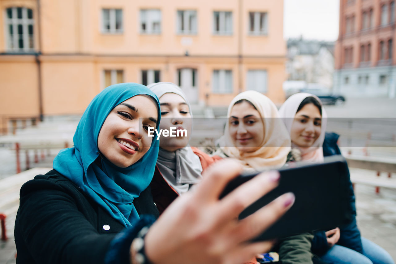 Young woman taking selfie with muslim female friends in city
