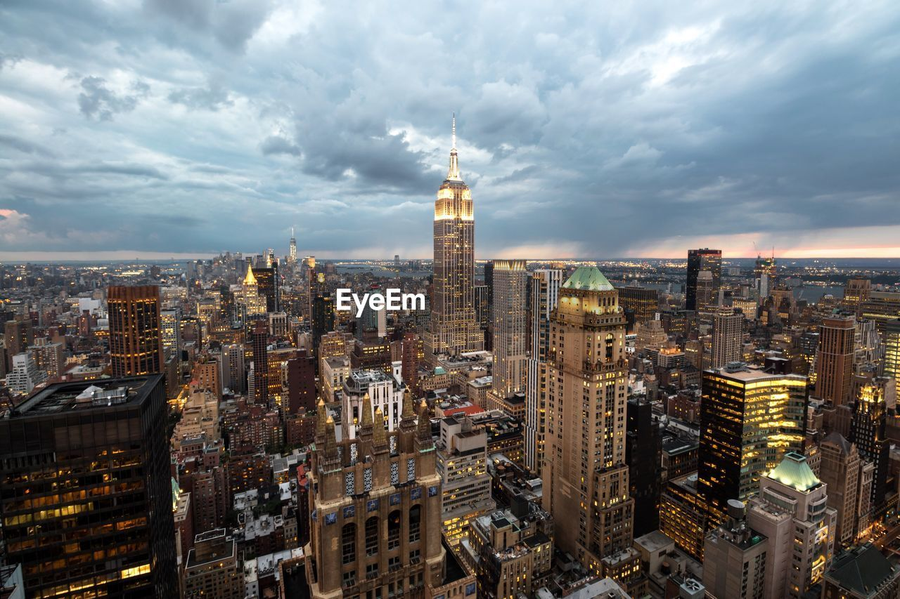 cityscape, architecture, skyscraper, city, building exterior, tower, tall - high, travel destinations, cloud - sky, built structure, sky, crowded, modern, urban skyline, outdoors, tall, illuminated, day