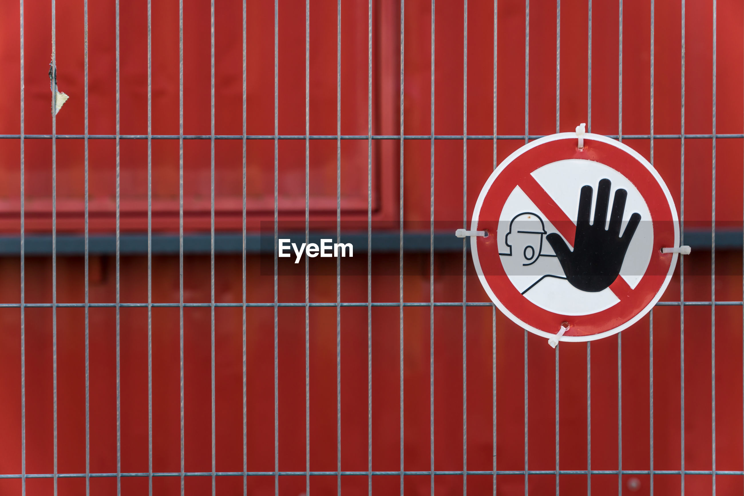 Close-up of do not enter sign on fence against red wall