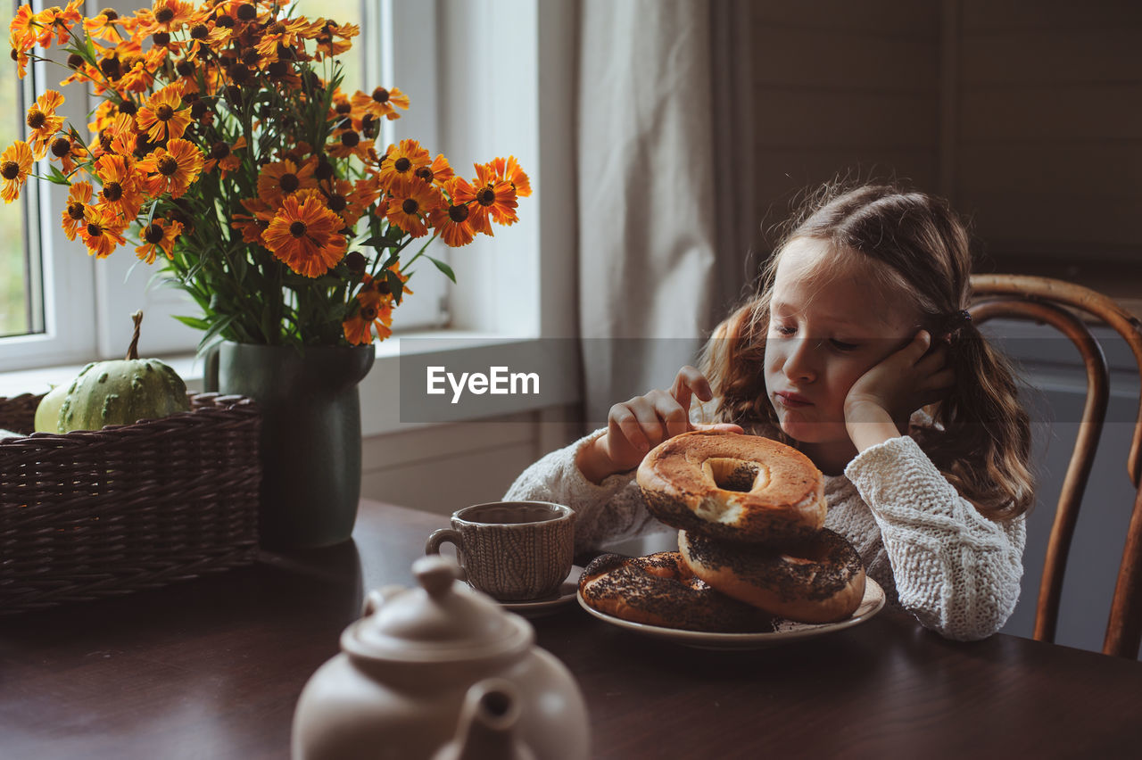 Cute girl having breakfast on table at home