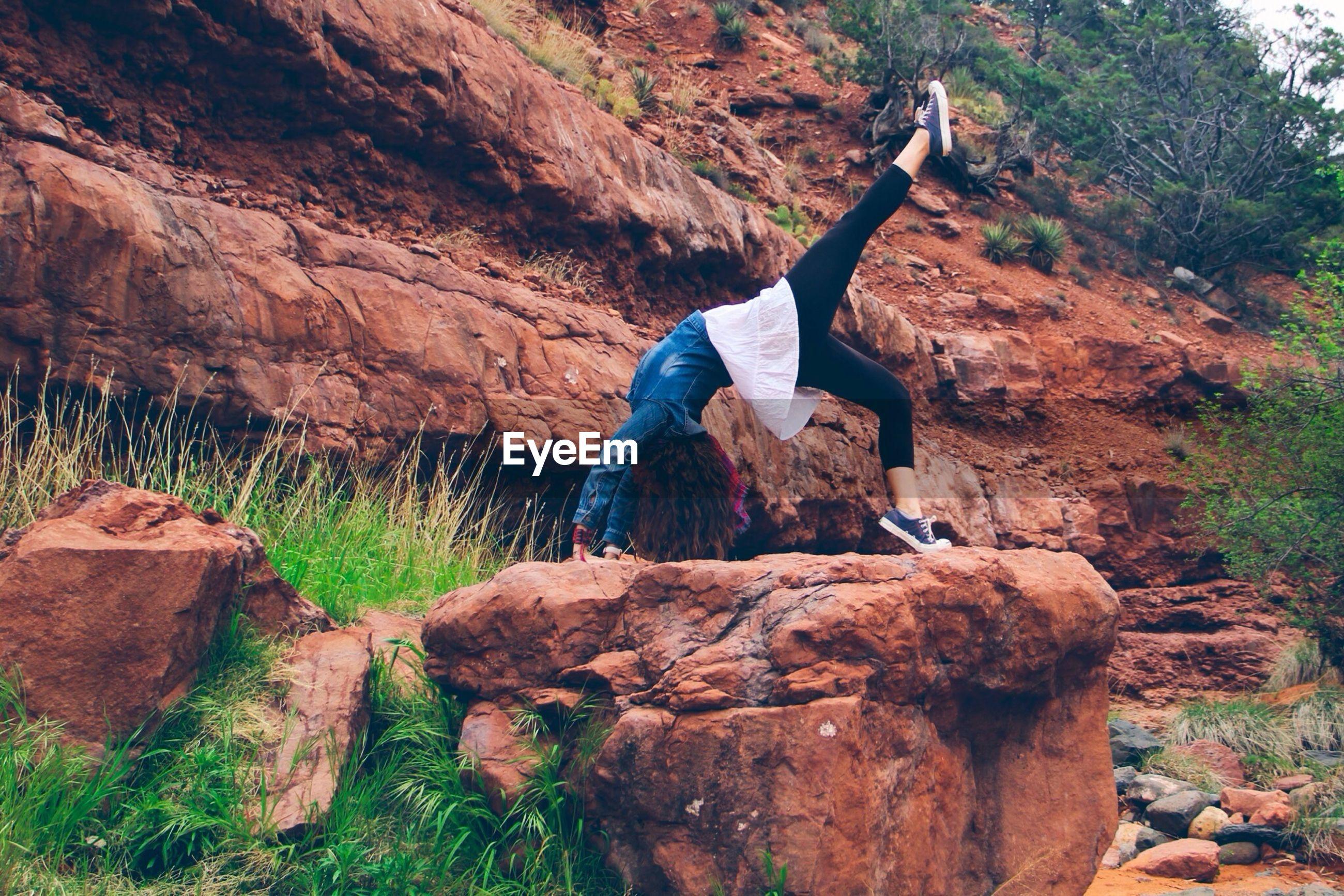 Woman doing bridge position on rocks