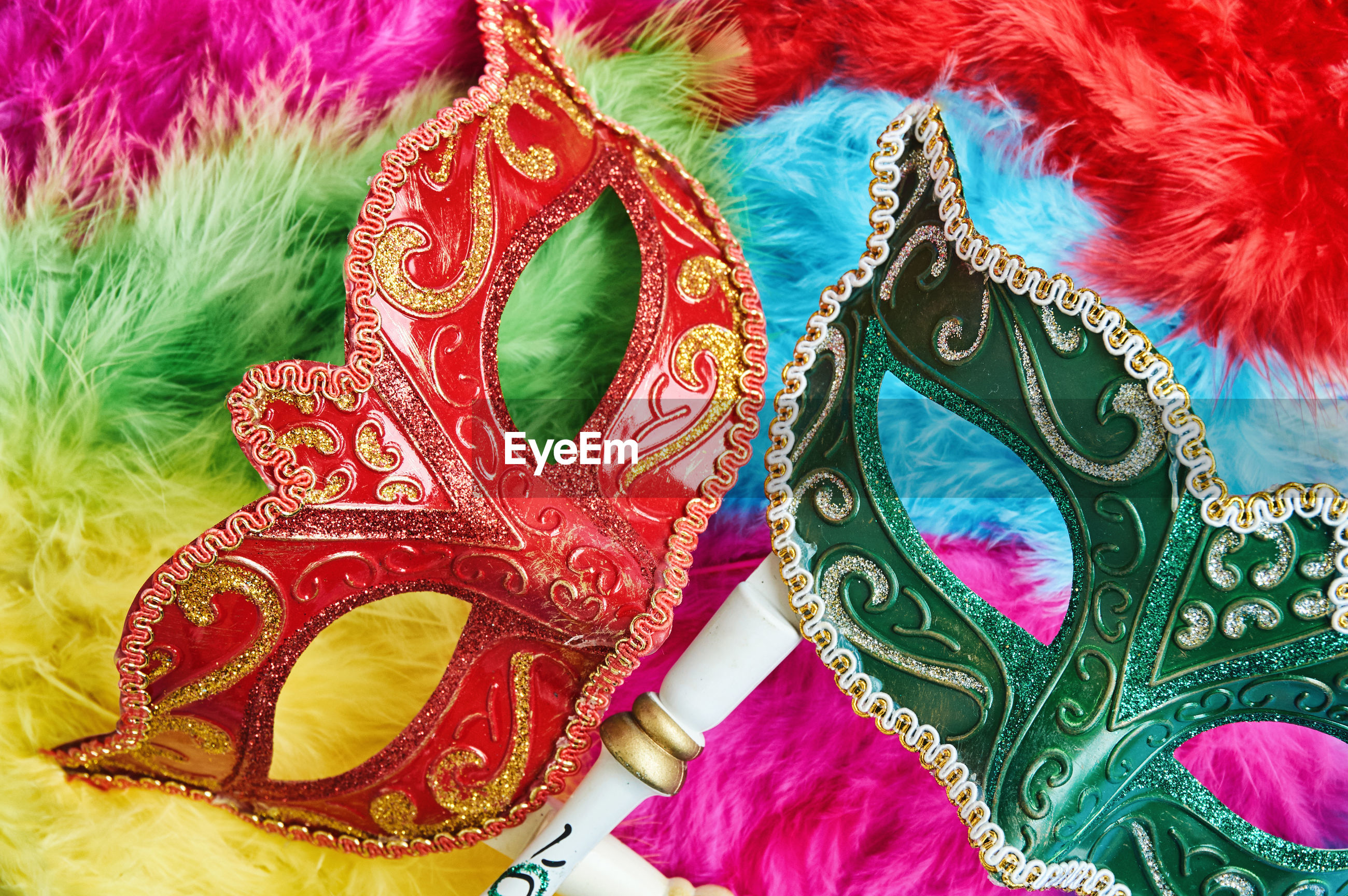 High angle view of masks on colorful feathers