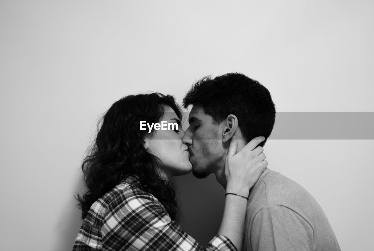 Side View Of Couple Kissing Against White Background