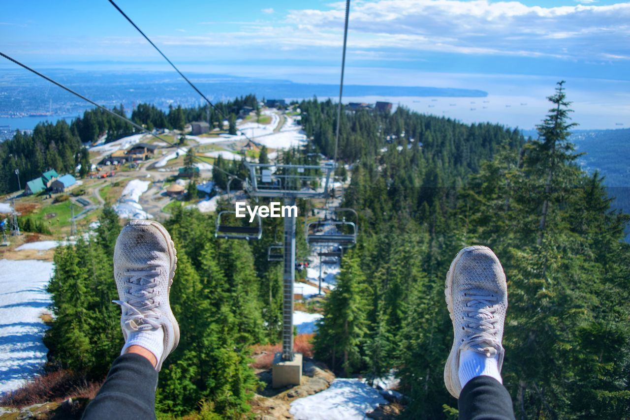 Low section of person wearing shoes while sitting in ski lift over mountain