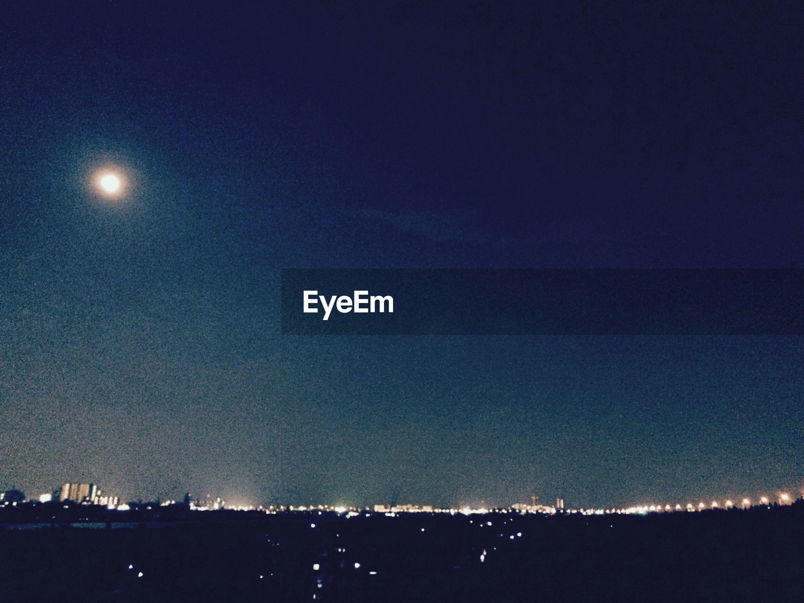 night, illuminated, moon, copy space, scenics, clear sky, sky, beauty in nature, tranquil scene, blue, full moon, tranquility, nature, light, dark, idyllic, dusk, astronomy, outdoors, cityscape
