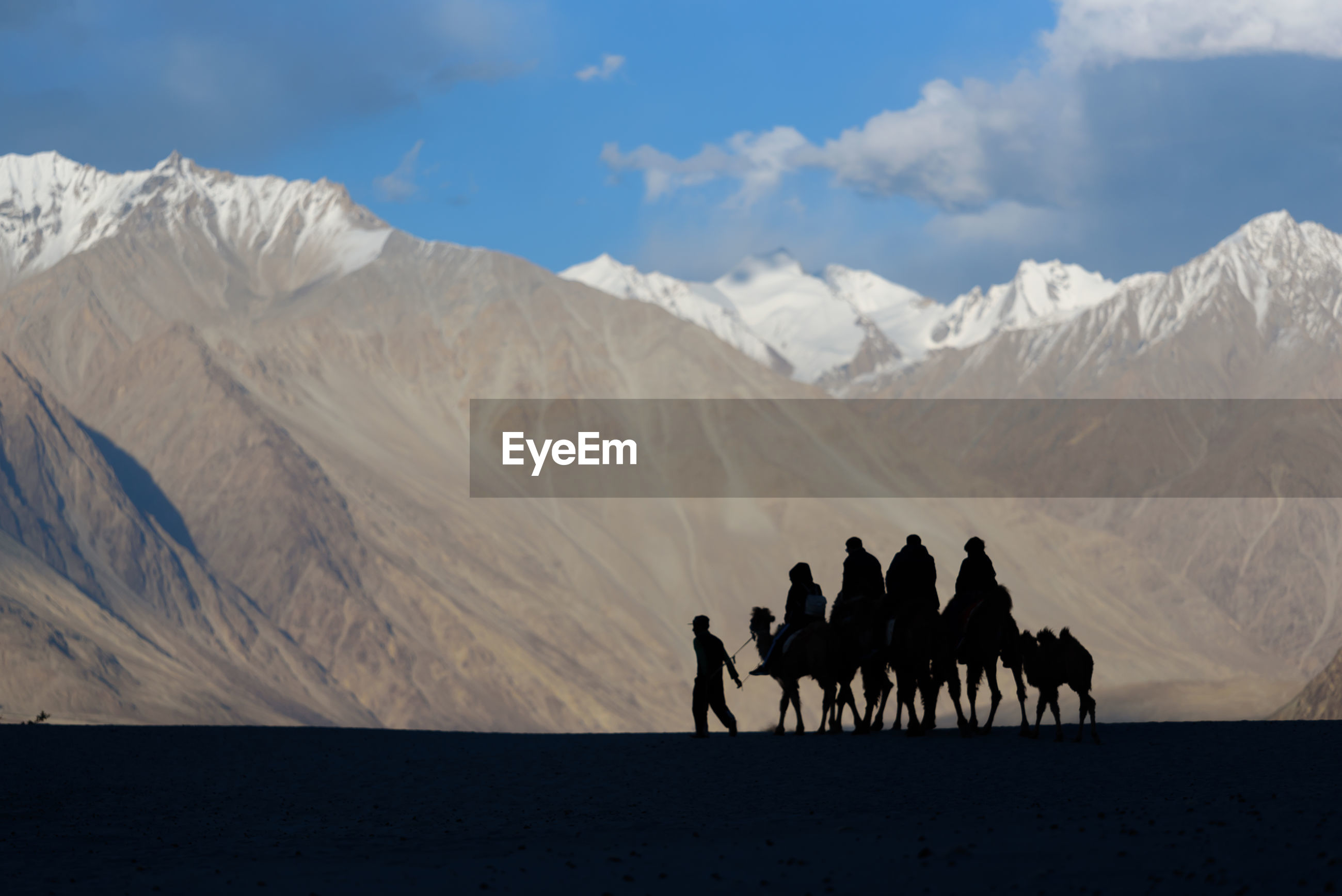 Silhouette people riding camels in desert against mountains