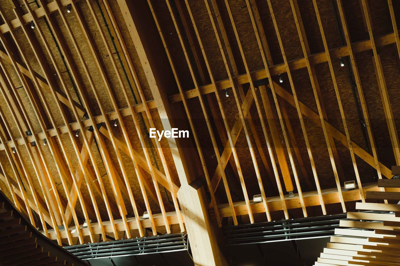 music, musical instrument, indoors, arts culture and entertainment, no people, musical equipment, pattern, in a row, wood - material, low angle view, repetition, metal, piano, architecture, string instrument, illuminated, built structure, musical instrument string, large group of objects, lighting equipment, ceiling