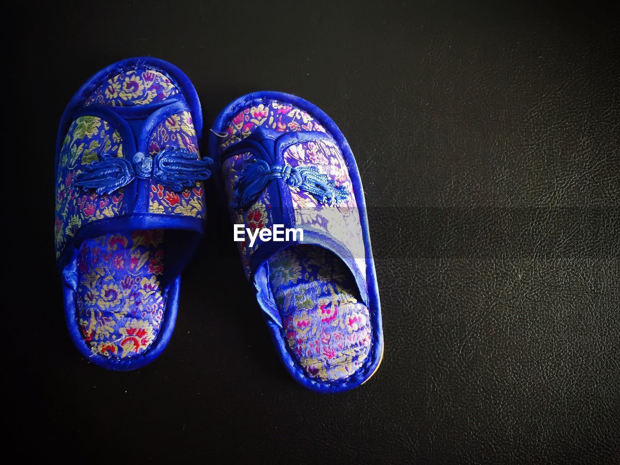blue, indoors, shoe, close-up, no people, pair, still life, studio shot, pattern, two objects, black background, high angle view, art and craft, creativity, multi colored, old, table, floral pattern, design, craft
