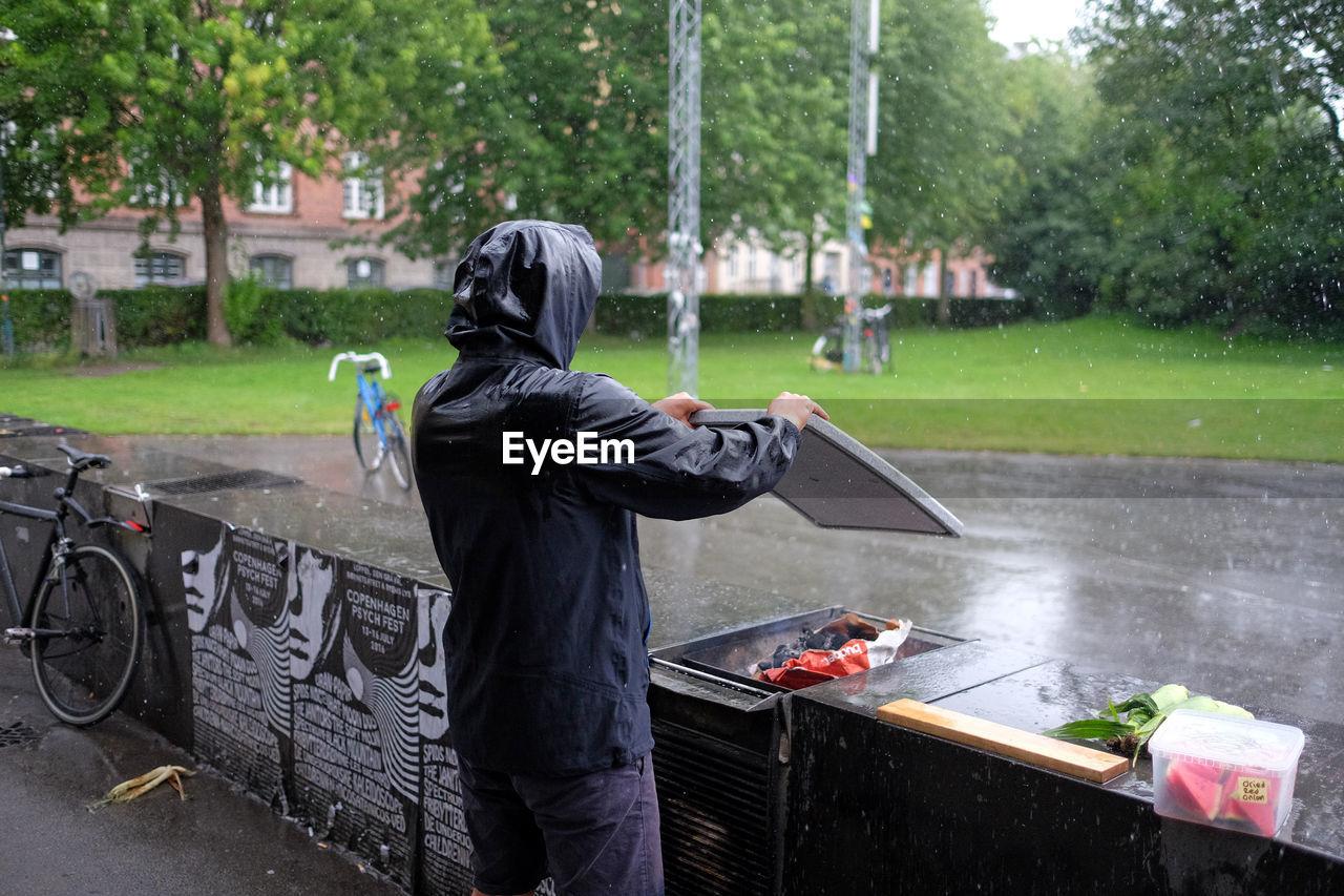 Rear View Of Man Wearing Hooded Shirt Preparing Barbeque At Yard
